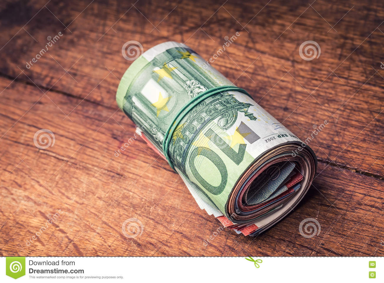Euro banknotes. Euro currency. Euro money. Close-up Of A Rolled Euro Banknotes On concrete or Wooden table