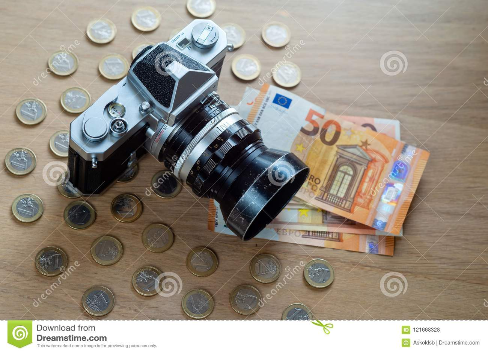 Euro banknoty, monety i kamera na lekkim drewnianym tle,