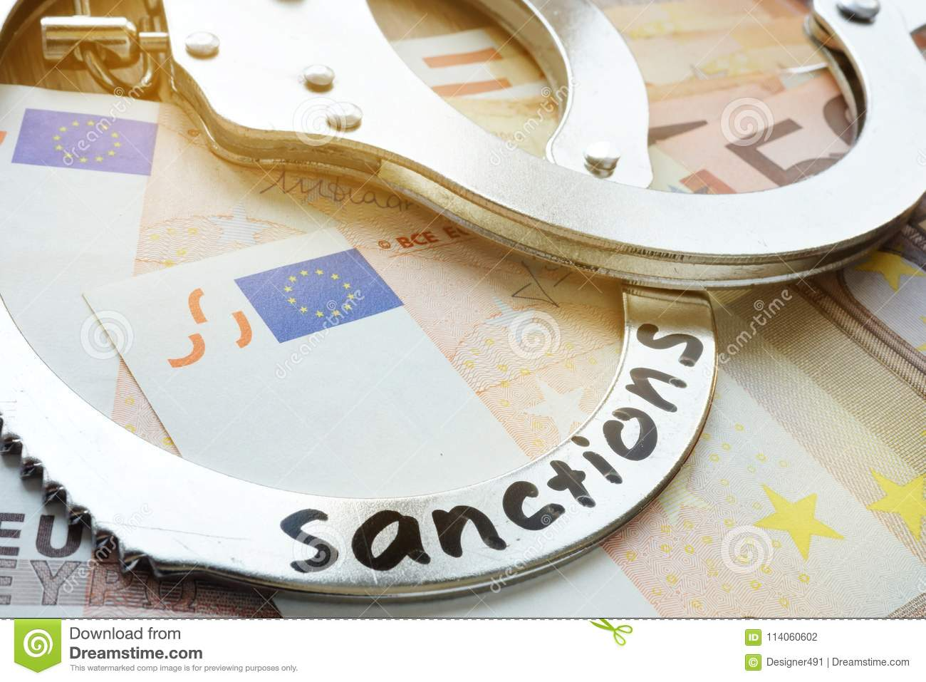 Euro bills and handcuffs with sanctions. Economical restrictive measures.
