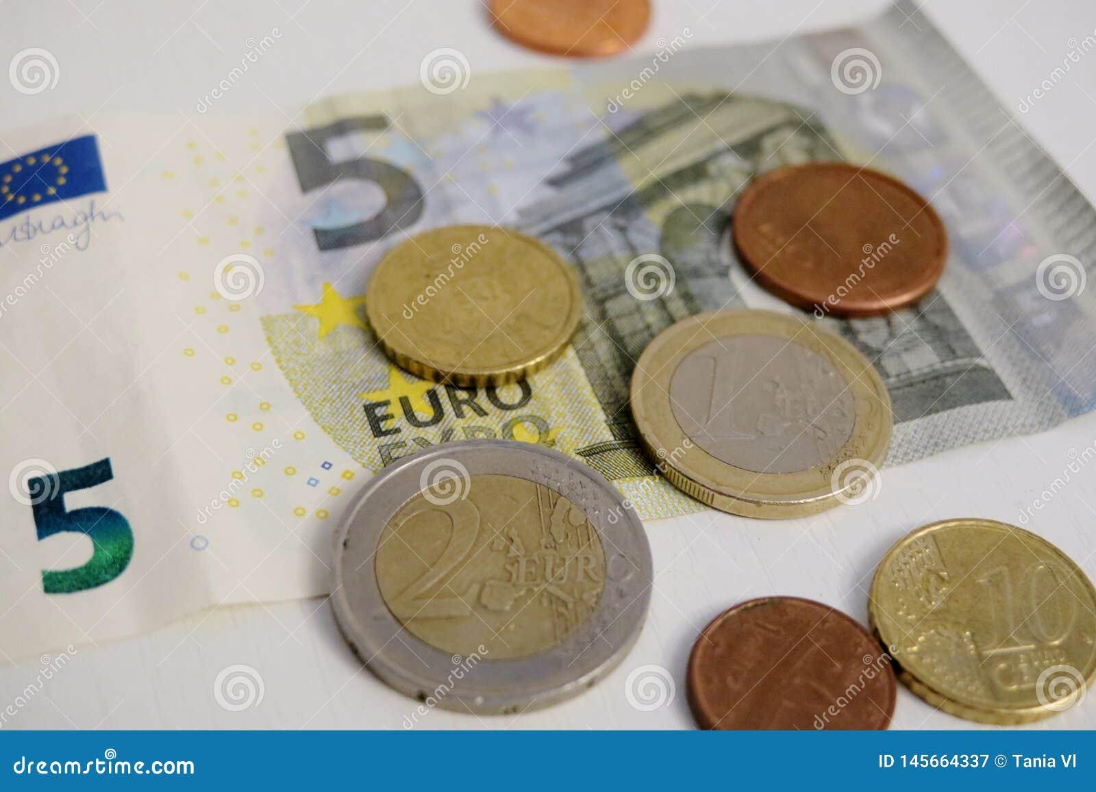 Euro cinco e uma moeda de um centavo em um close-up branco do fundo