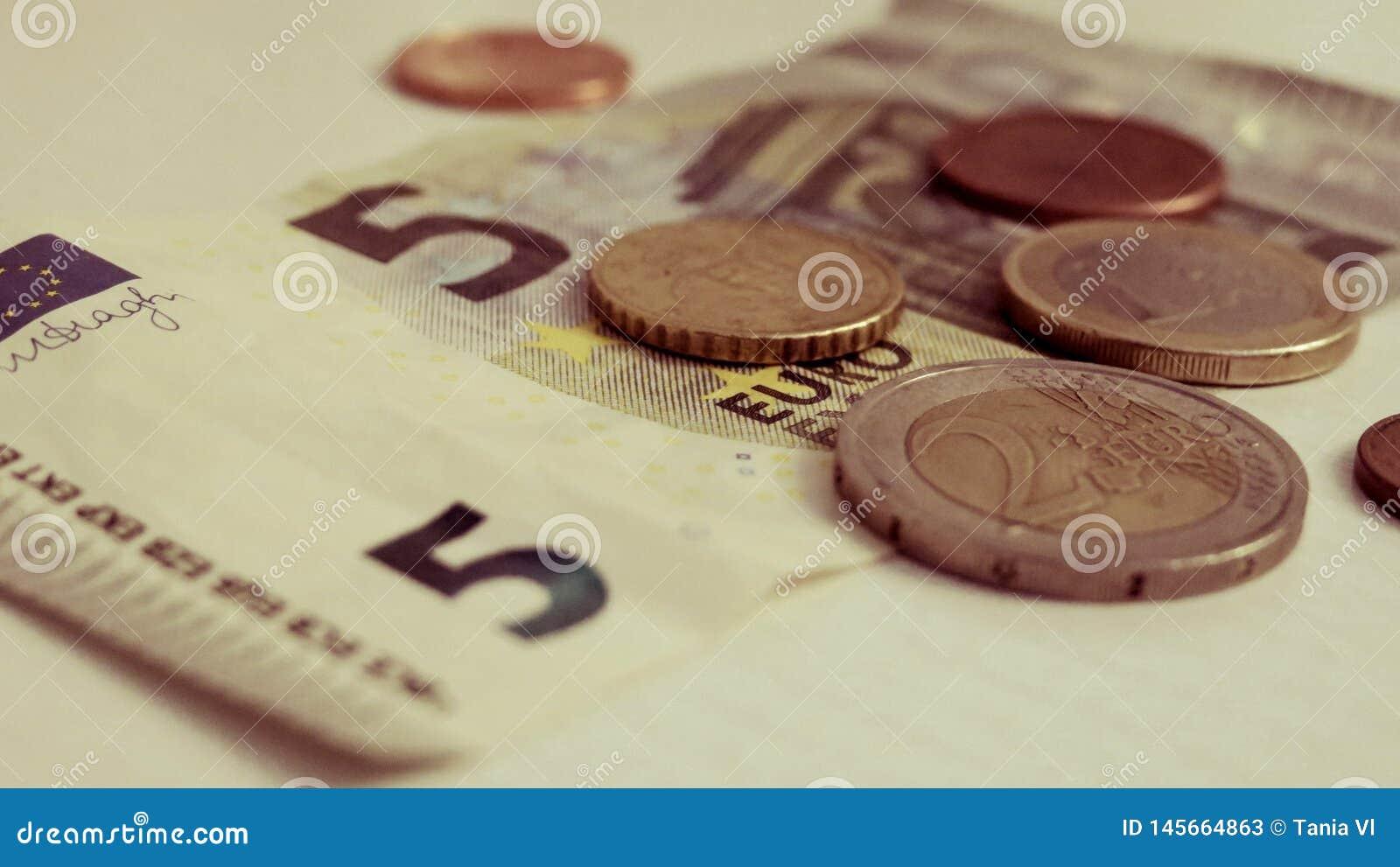Euro cinque e un penny su un primo piano bianco del fondo