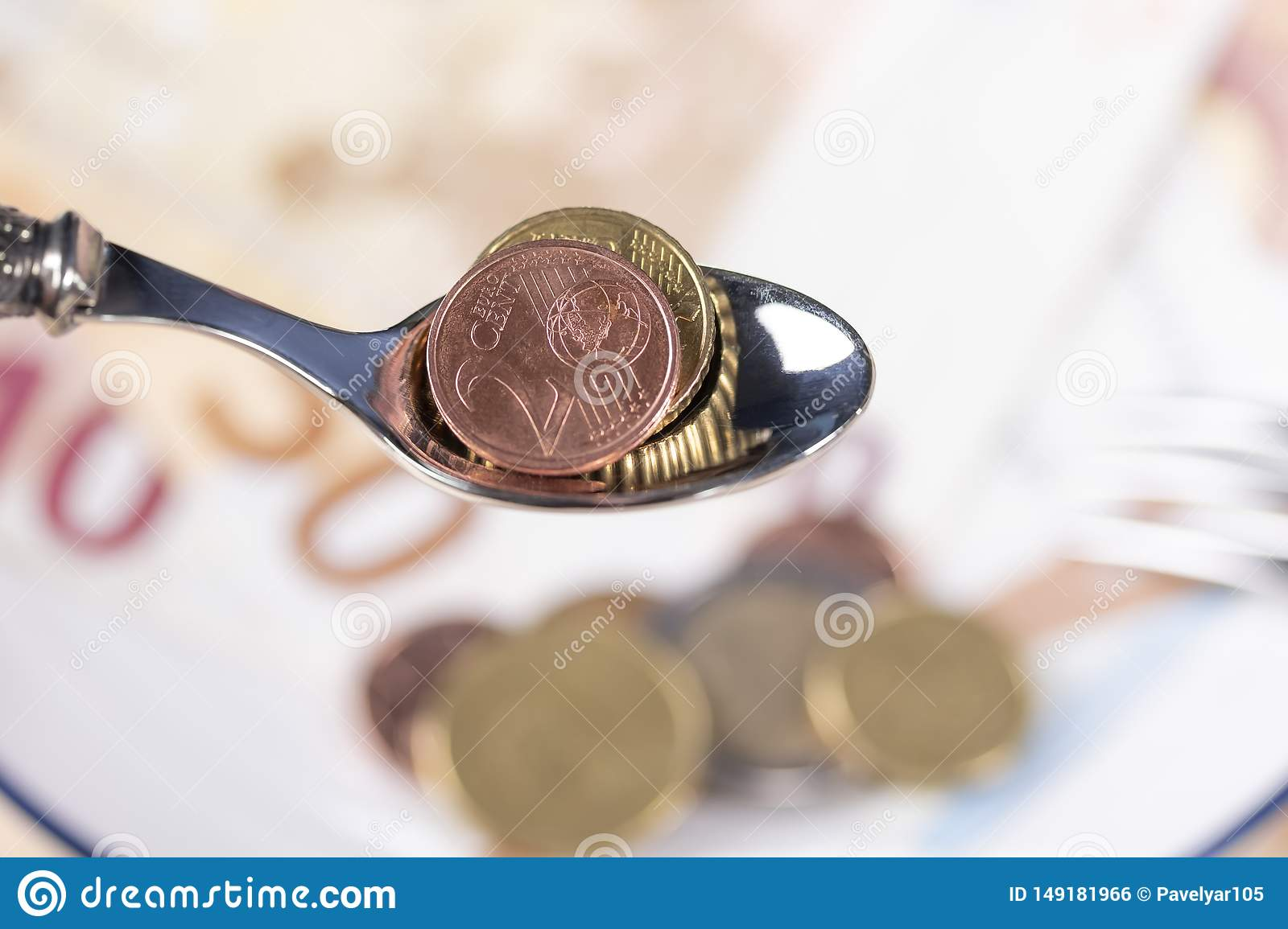 Euro coins in a dessert spoon over a plate of money with a blue border