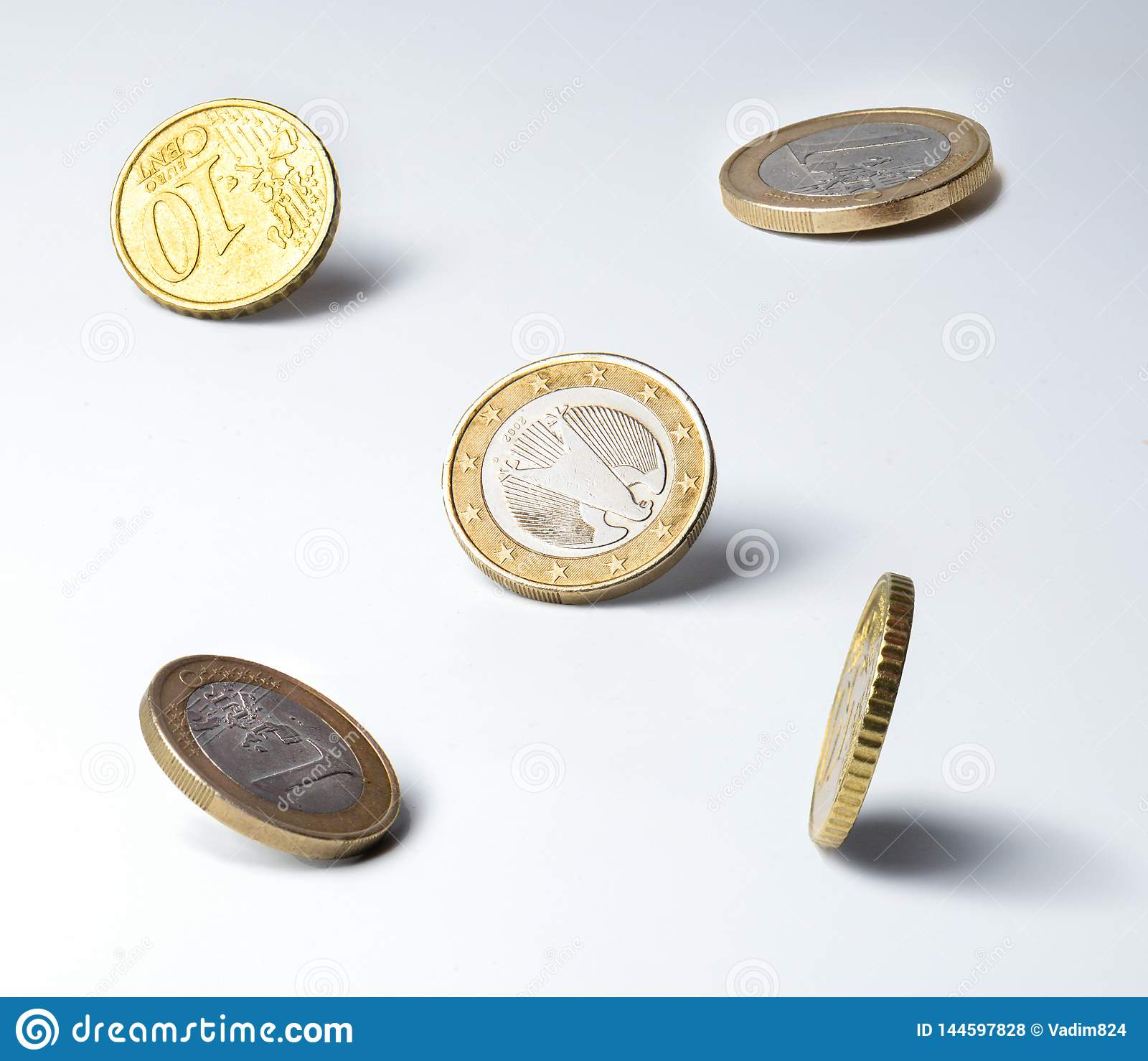 Euro coins in an unstable position on the edge. Clear shadows. Close quarters. Symbol of finance, money circulation, market