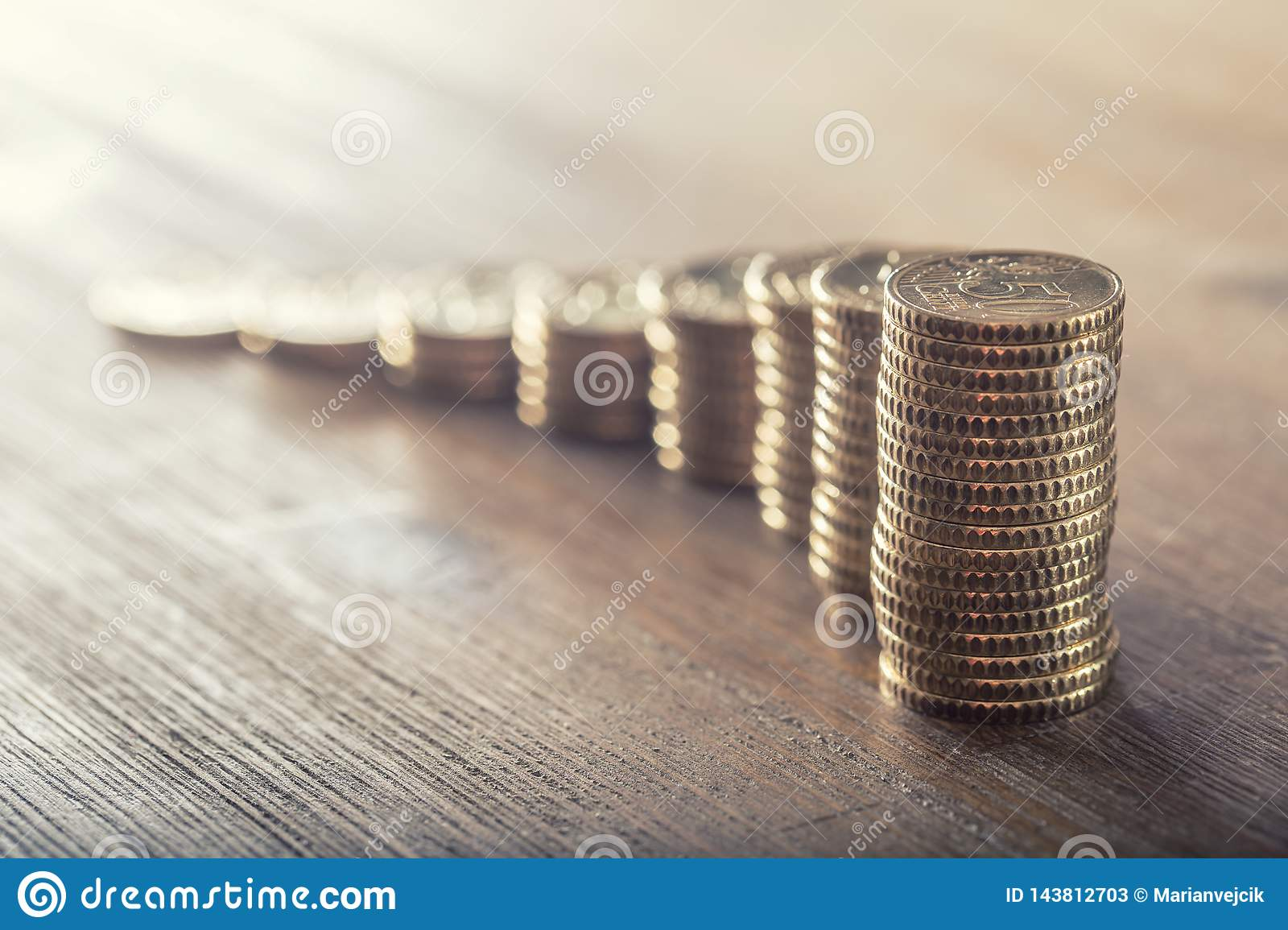 Euro coisn on a wooden table with a growth effect. Close-up european money and currency