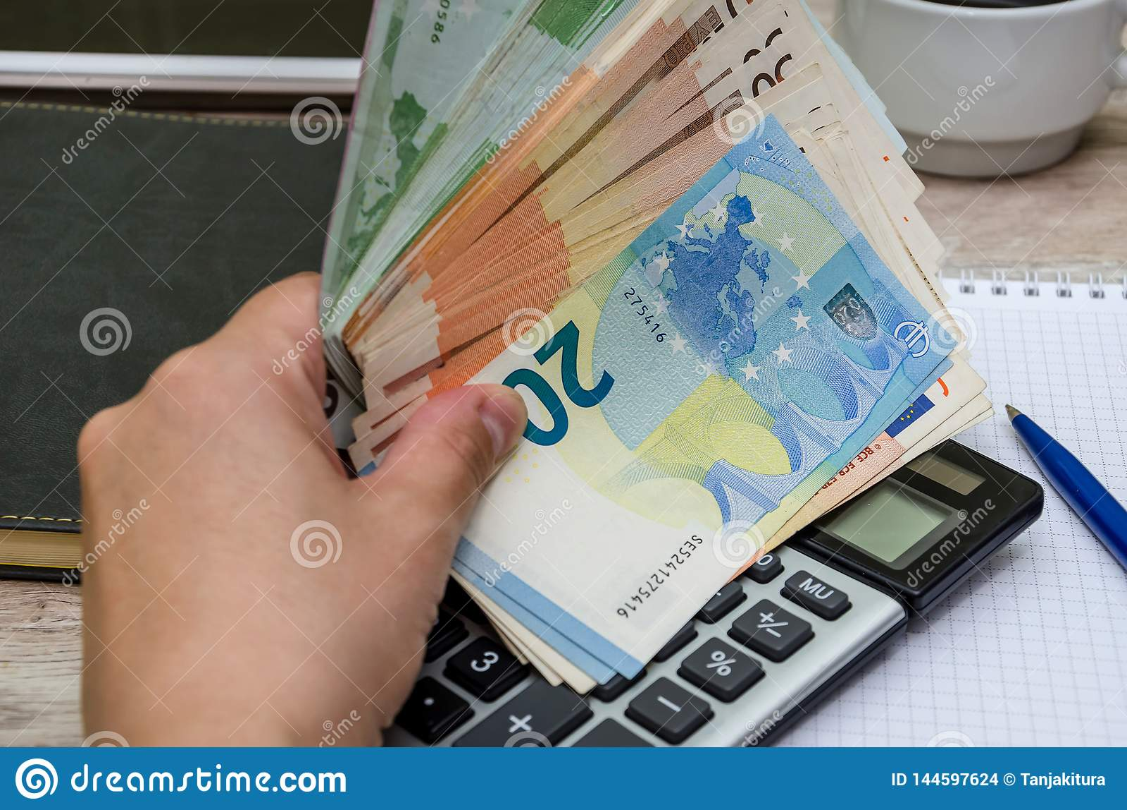 Euro in der Hand auf dem Hintergrund einer Notizbuch- und Taschenrechnernahaufnahme