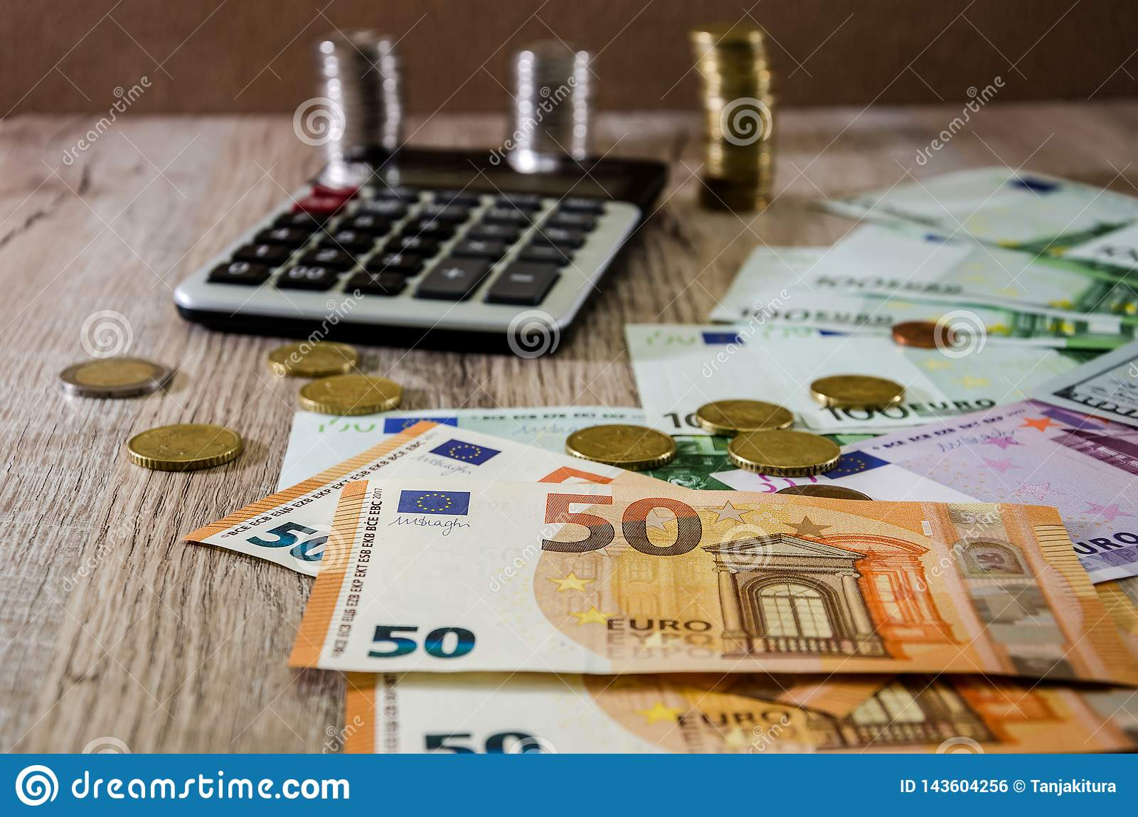 Euro, dollars, cents and calculator spread out on a wooden background