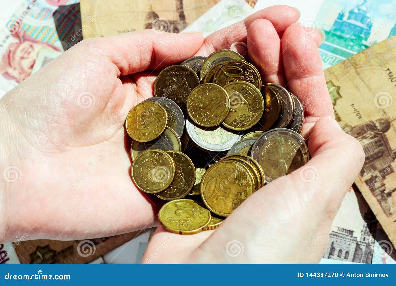 Euro y centavos euro en las manos femeninas con el fondo del billete de banco