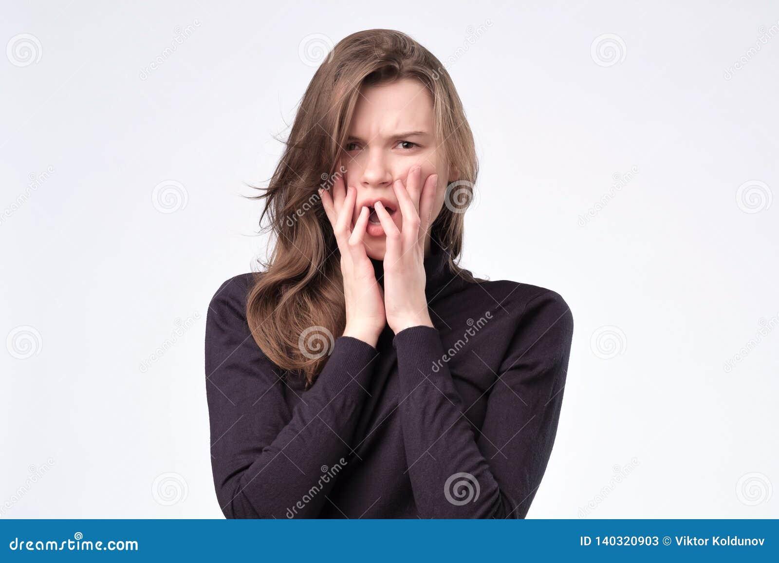 Europäische hübsche junge Frau erschrocken, ängstlich und besorgt, ihre Fingernägel beißend
