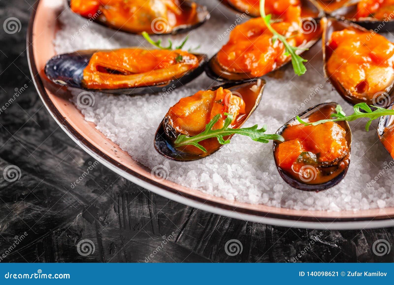 Europäische Küche Marinierte Miesmuscheln in der Tomatensauce mit Rosmarin, Knoblauch, Paprika Servierteller im Restaurant auf ei
