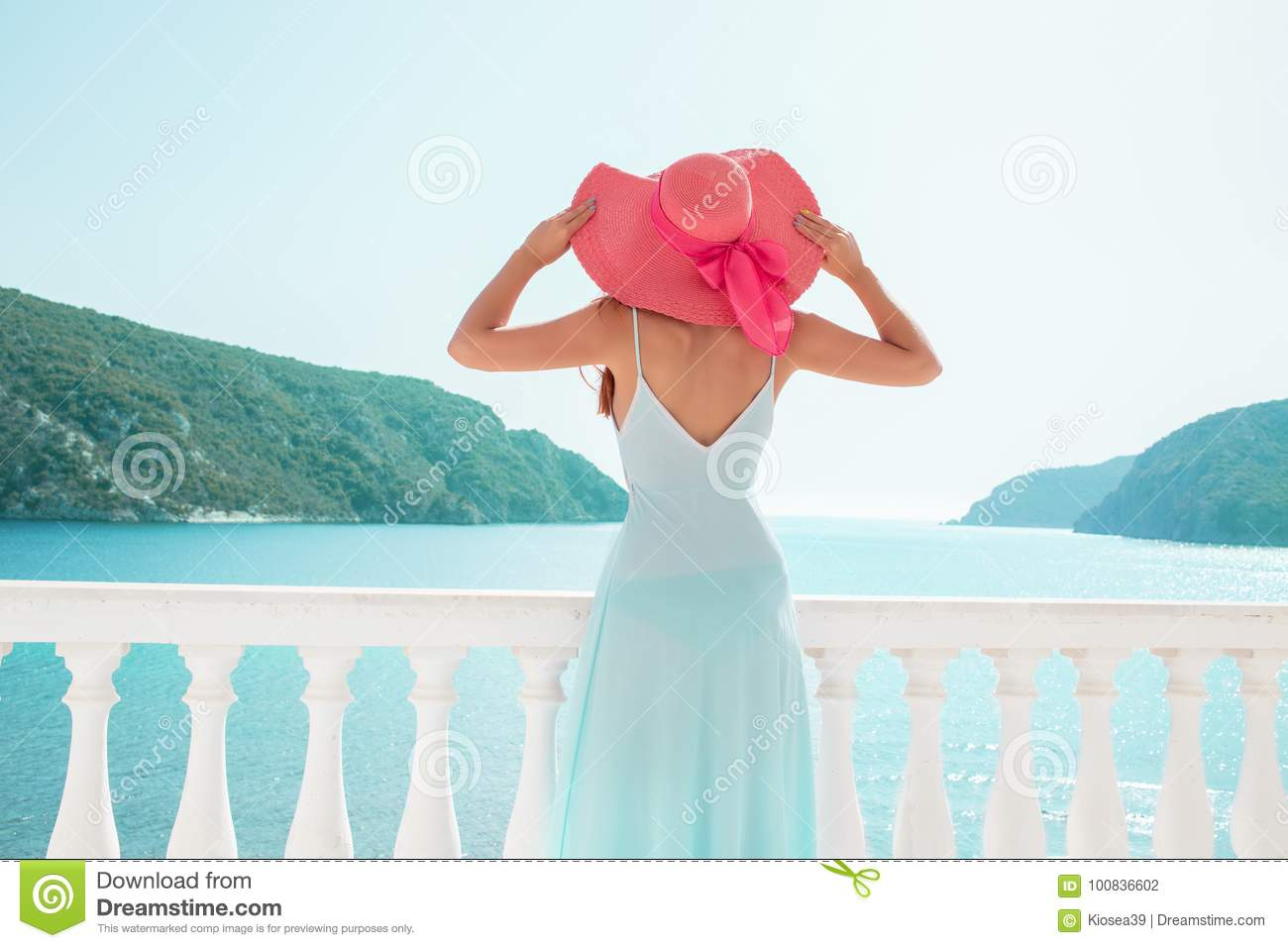 Europe Greece travel vacation. Woman looking at sea view. Elegant young lady living fancy jetset lifestyle wearing dress on holida