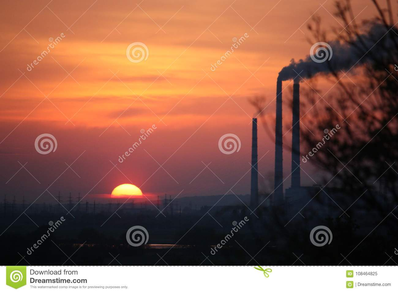 Europe. Poland. Ecology. Smoky chimneys of the factory in the sunset. Autumn 2017