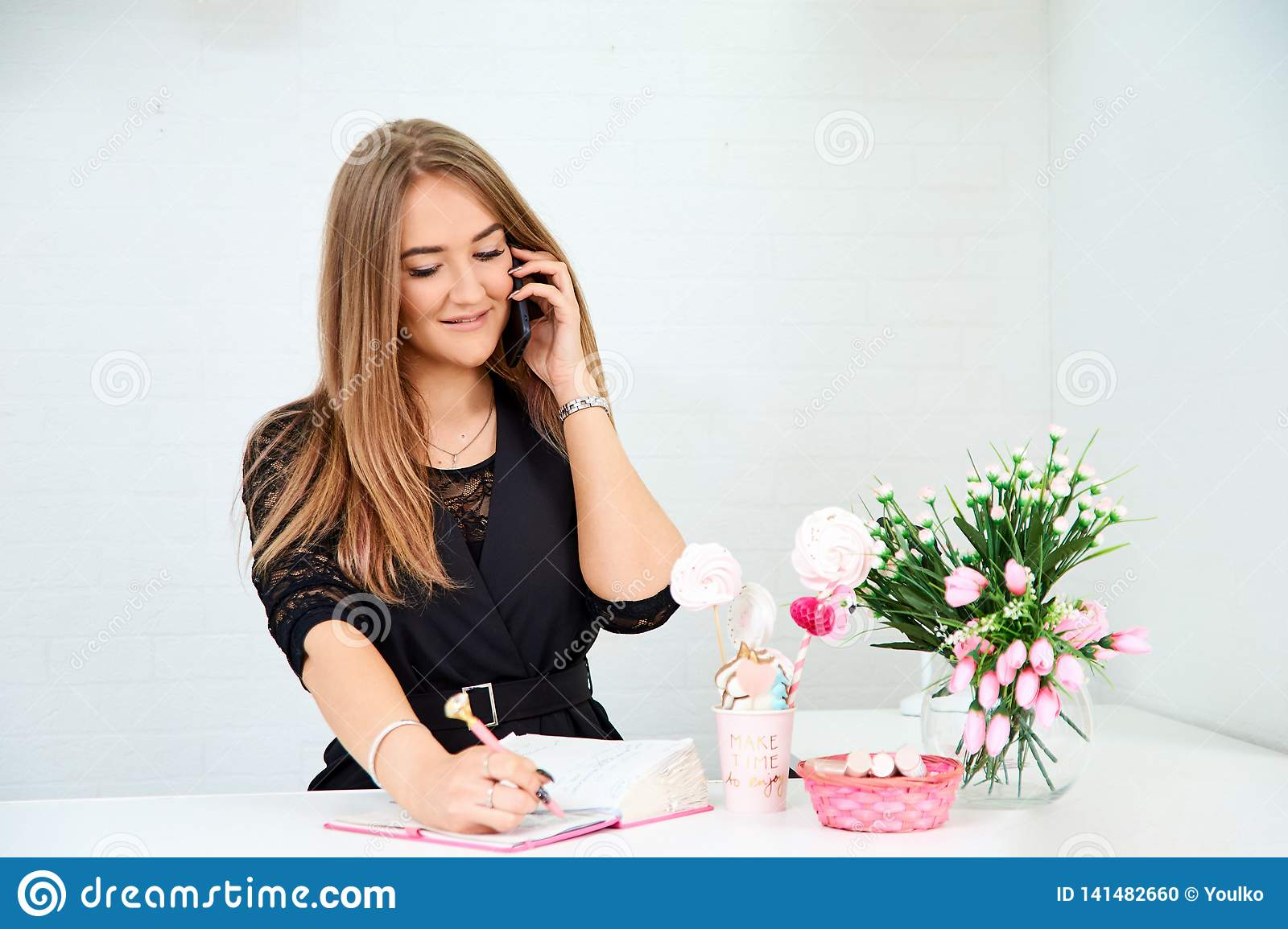 beautiful European girl takes a call on the phone and writes in a notebook on a white background. Nearby are flowers and