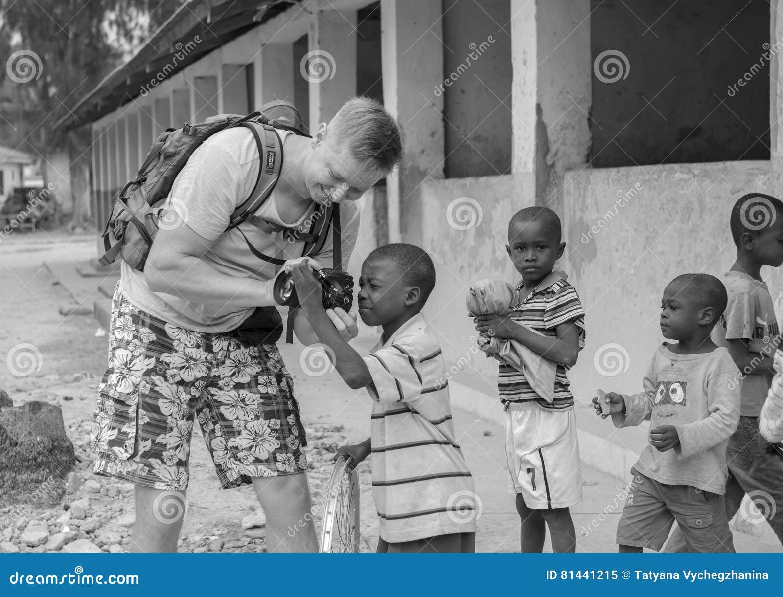 European tourist showing camera to african children
