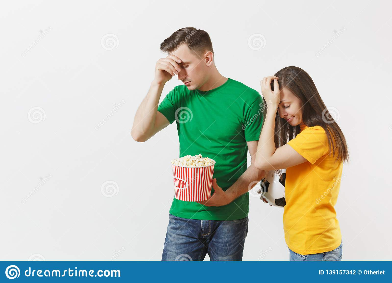 European upset couple, woman, man, football fans in yellow green t-shirt cheer up support team with soccer ball bucket