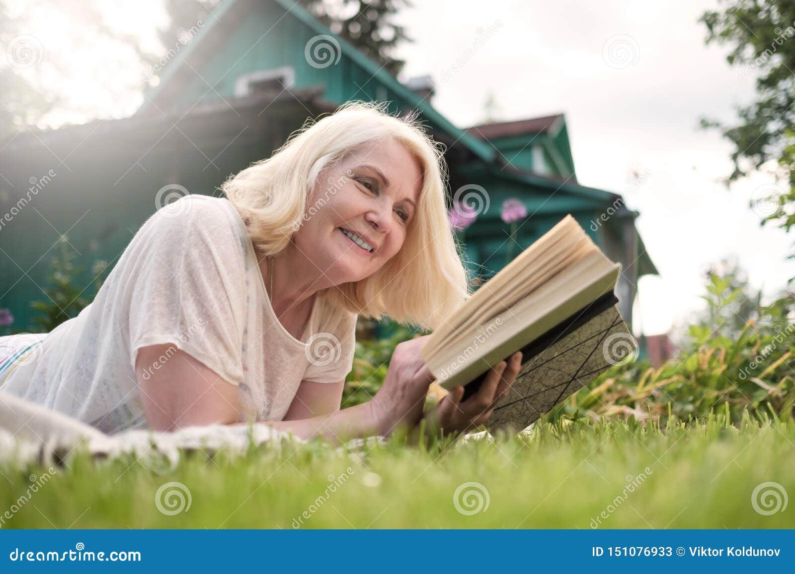 Europejczyk blondynki dojrzała kobieta czyta książkę w ogródzie