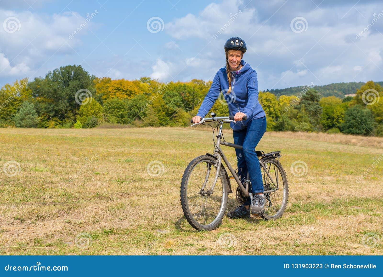 Europejska kobieta na rowerze górskim w niemieckiej naturze