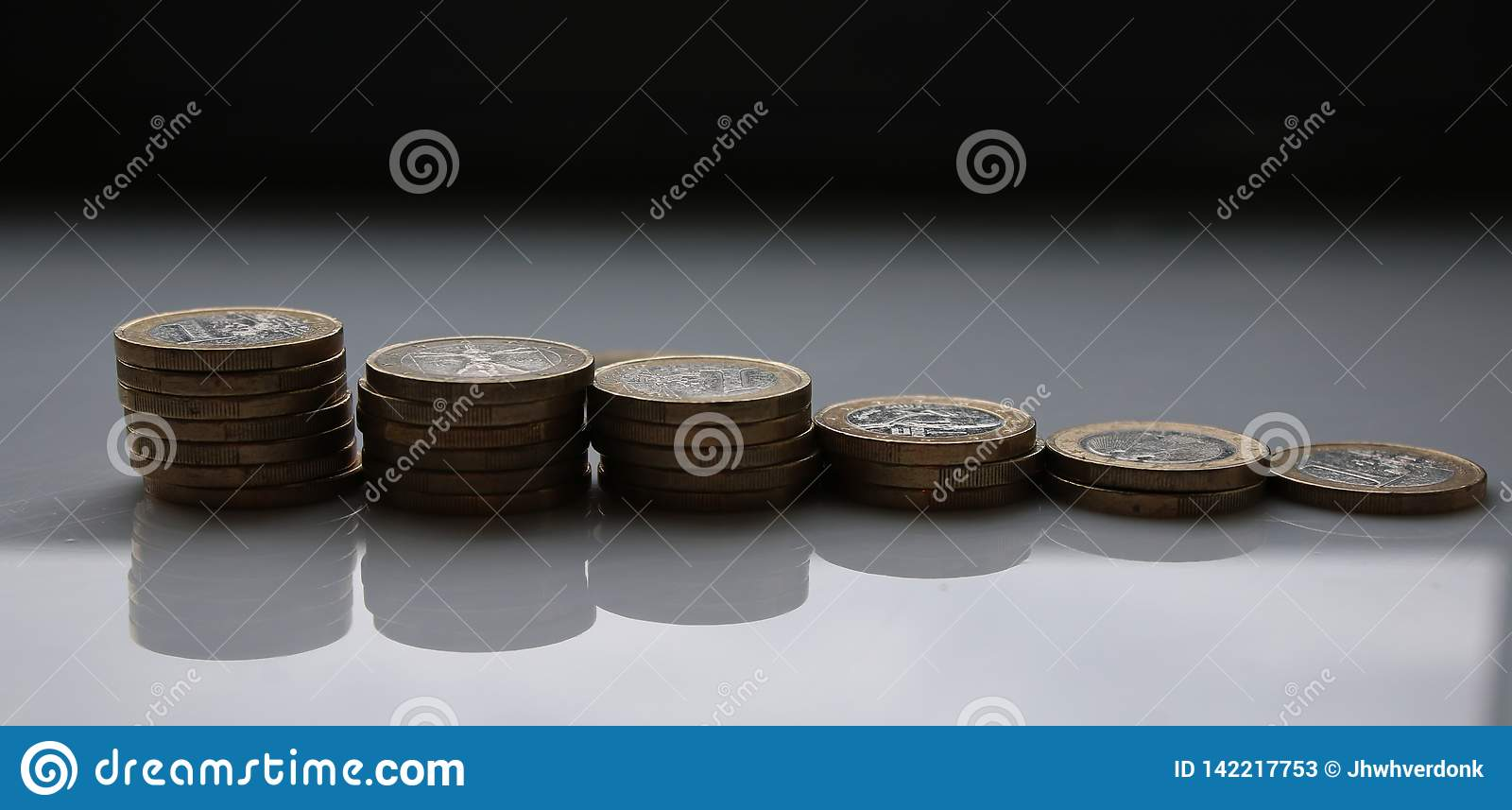 Euros stacked in piles with a white background and shadows visible
