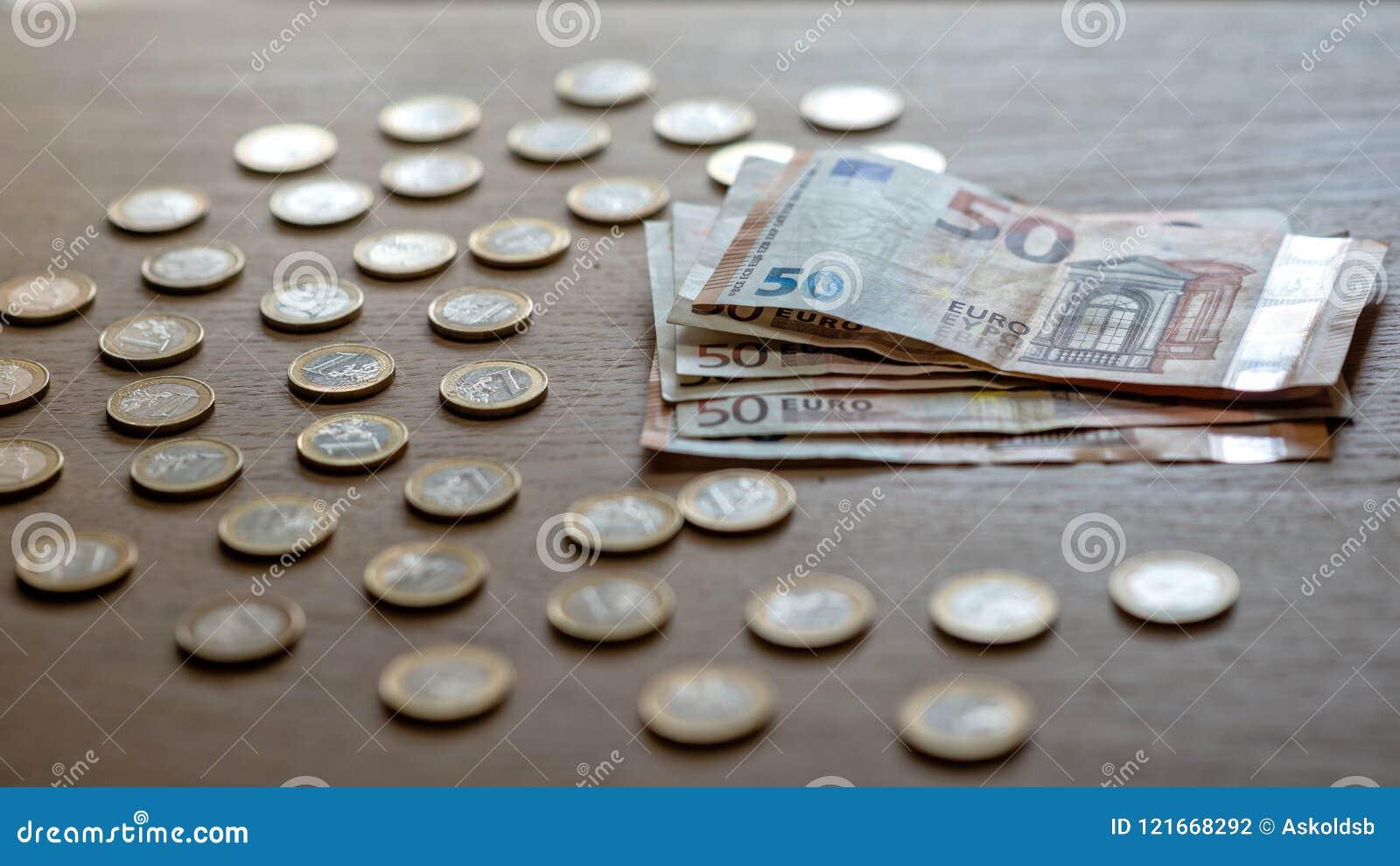 50 eurosedlar och 1 euro mynt på en ljus wood bakgrund