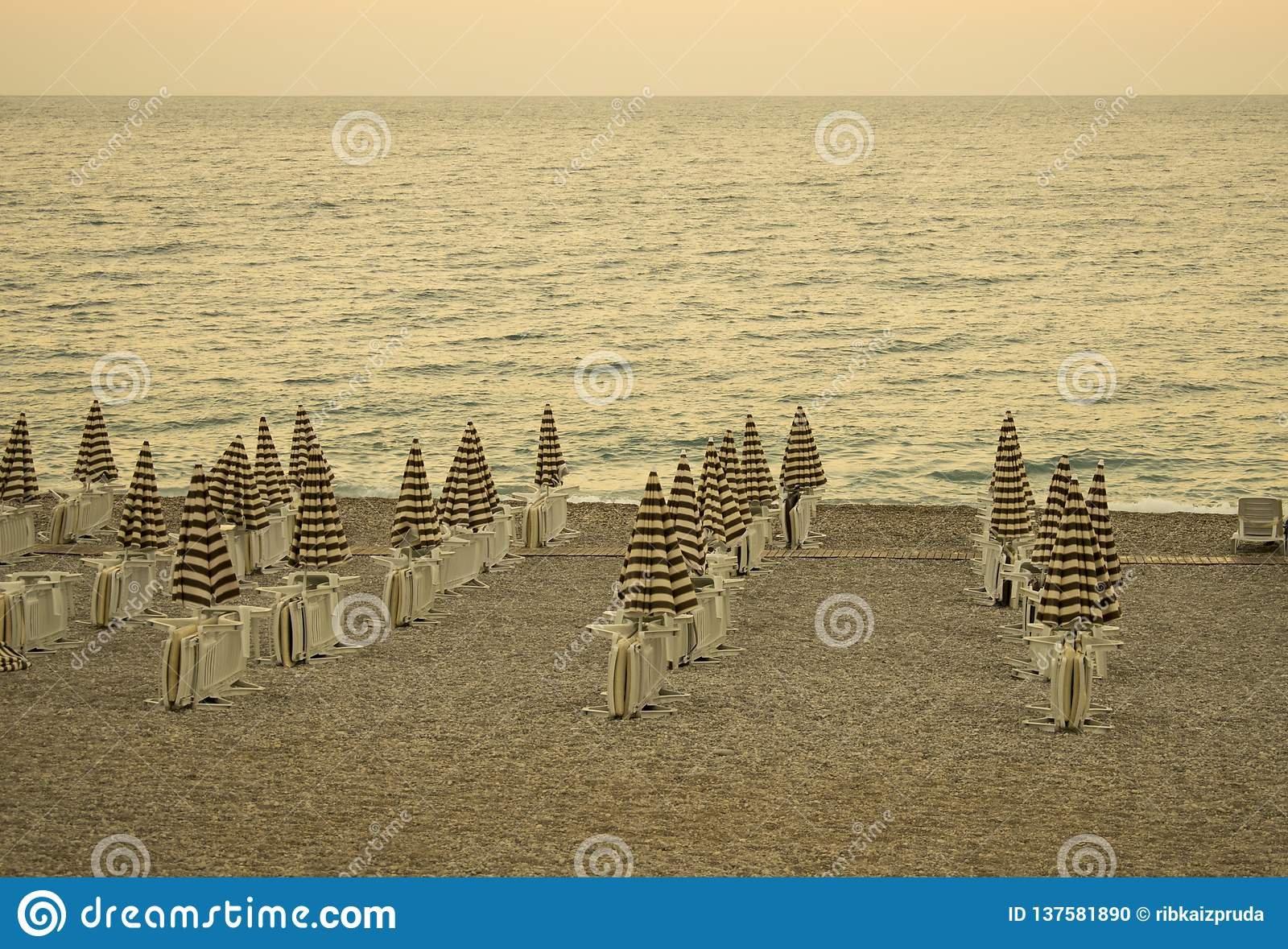 Evening empty beach with chairs and striped umbrellas. Resort landscape. Vintage retro filter