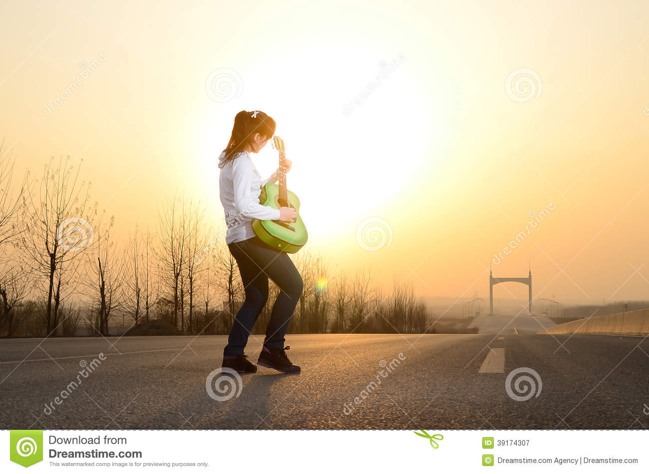 In the evening, girl playing guitar on the road