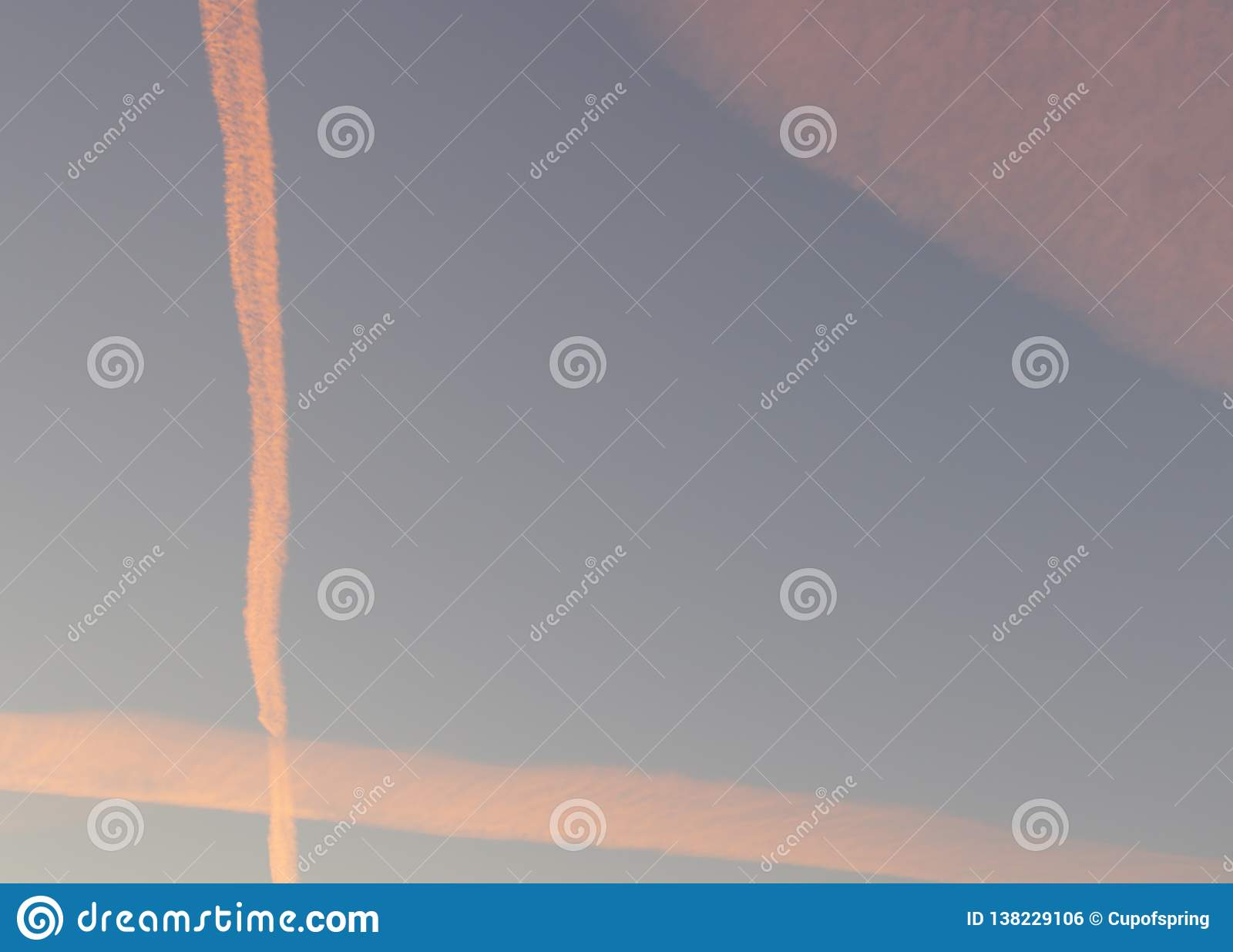 Evening golden hours blue sky with clouds and orange condensation trails of planes
