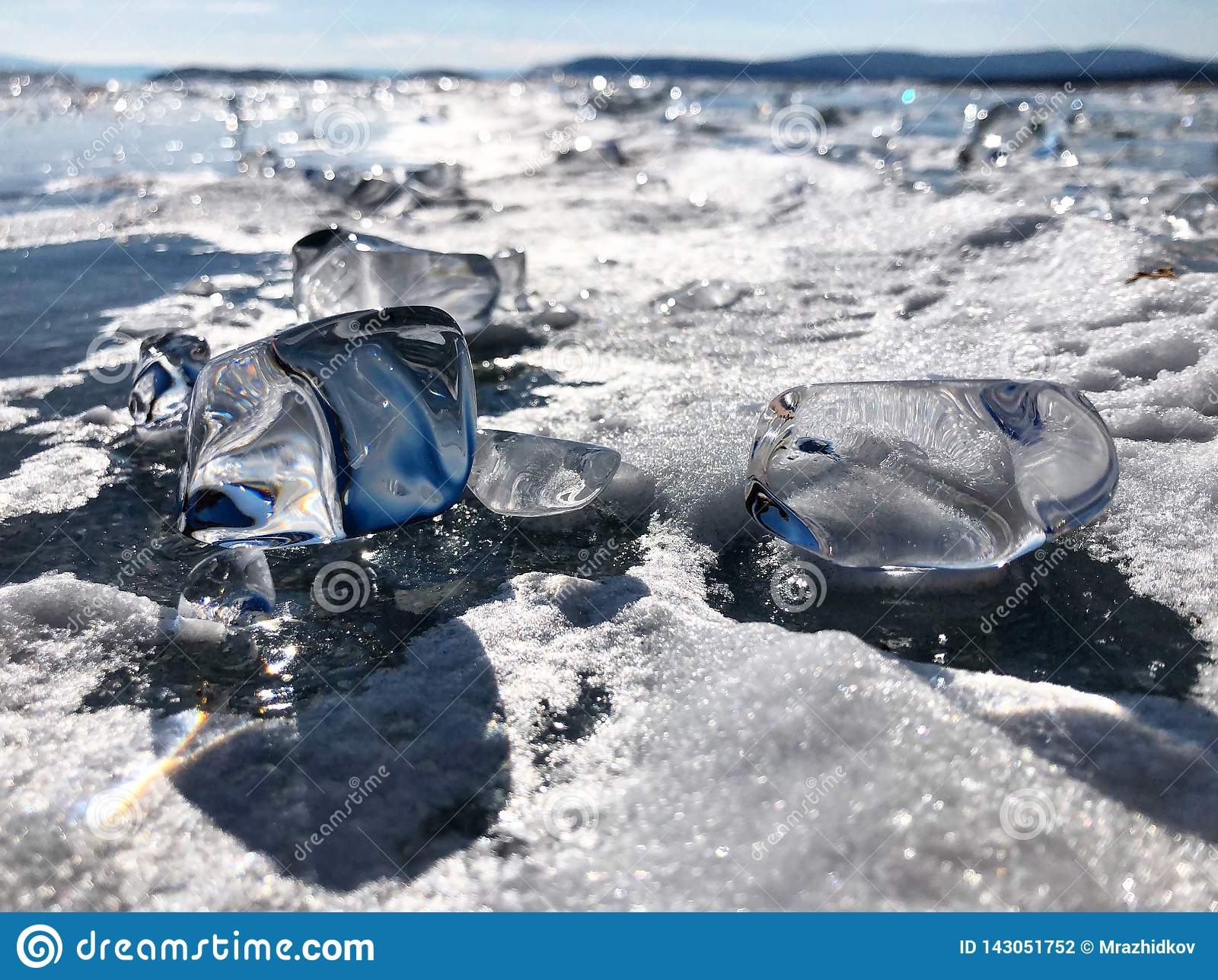 Shiny ice cubes.Evening view. Cracks on the surface of the blue ice. Frozen lake Baikal in winter mountains. It is snowing. The hi