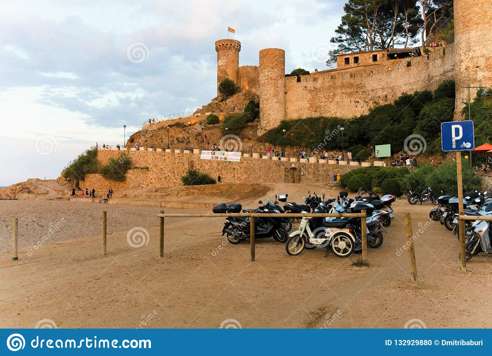 Tossa de Mar, Catalonia, Spain, August 2018. View of the fortress and parking of motorcycles at sunset.