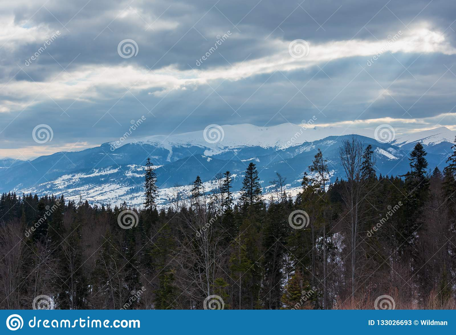 Evening Winter Mountain Ridge And Sun Rays From Cloudy Sky