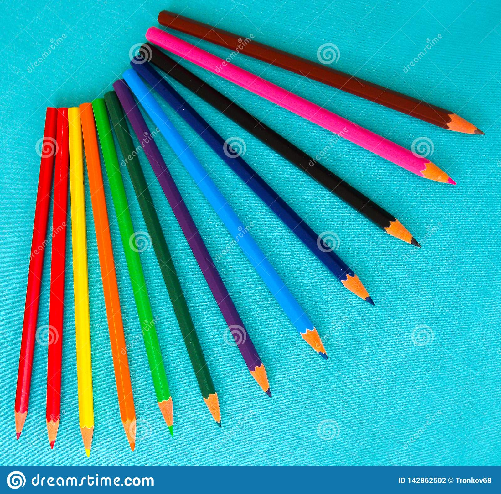 A set of children`s, colored pencils on a turquoise background.