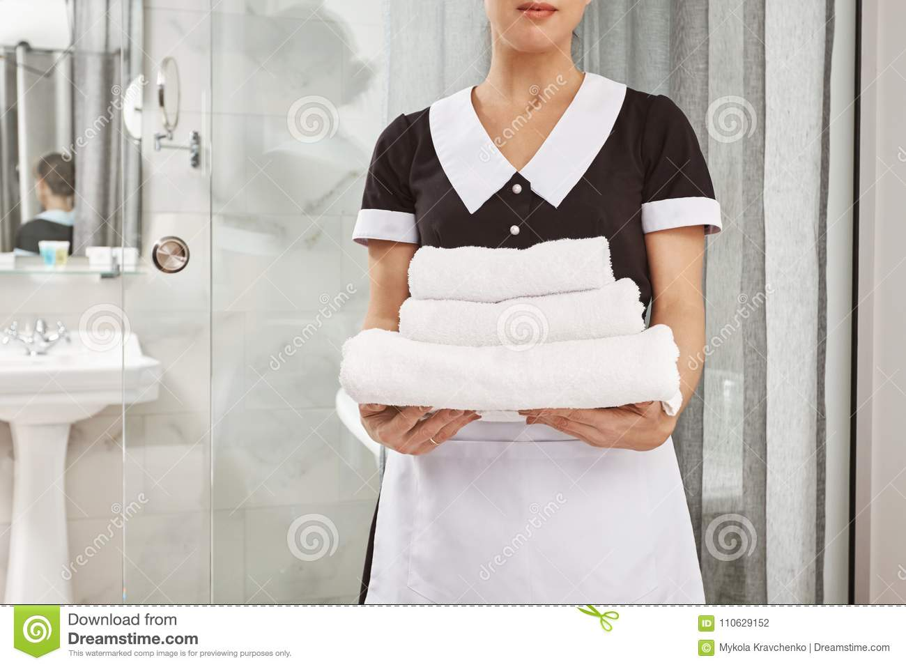 Everything is fresh and clean. Cropped portrait of housecleaner in maid uniform holding pack of white towels. Employee