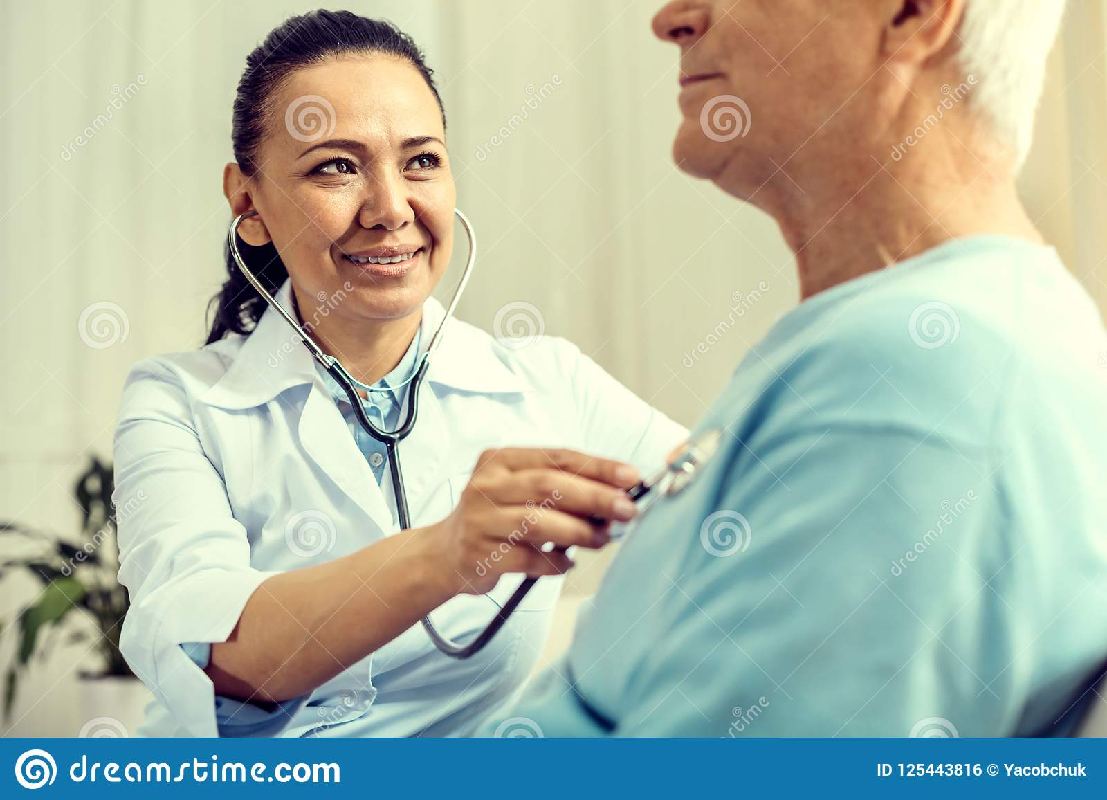 Beaming female doctor listening to heart beating