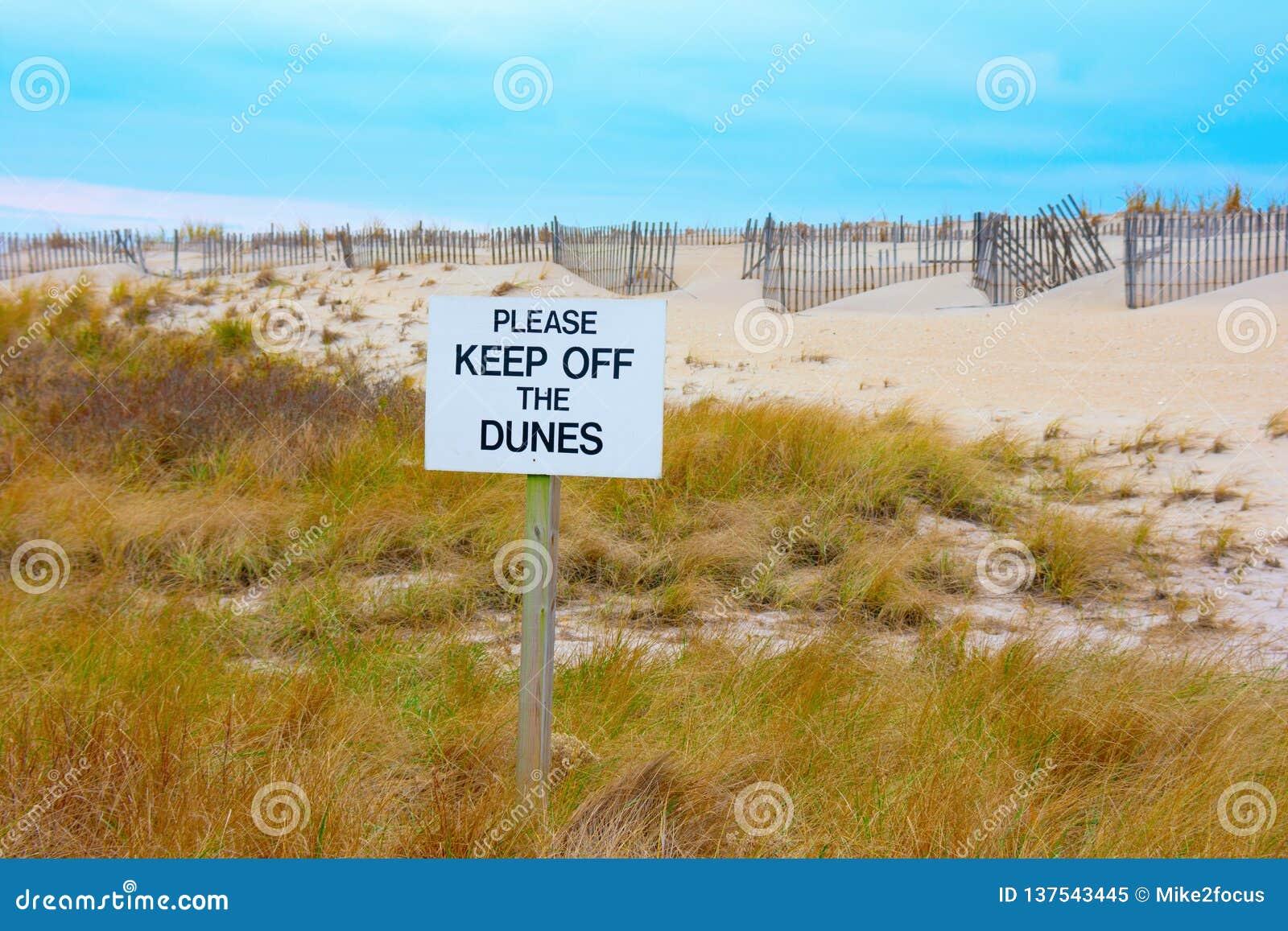 EVITE POR FAVOR LAS DUNAS firman con las dunas hermosas y el fondo del cielo azul
