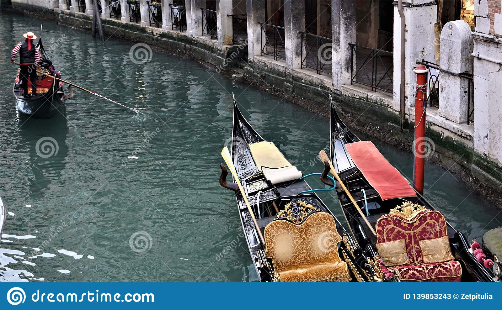 A channel with two gondolas and a gondolier floating near them in Venice, Italy