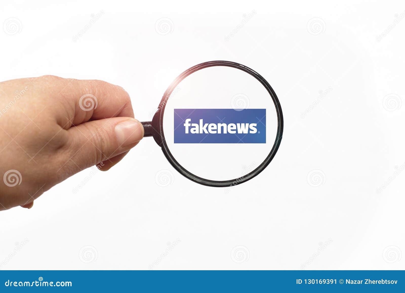 EVPATORIA, CRIMEA, UKRAINA, MARZEC, 12,2018 szkieł w ręce i Sfałszowanym wiadomości słowie na białym tle - Powiększający -