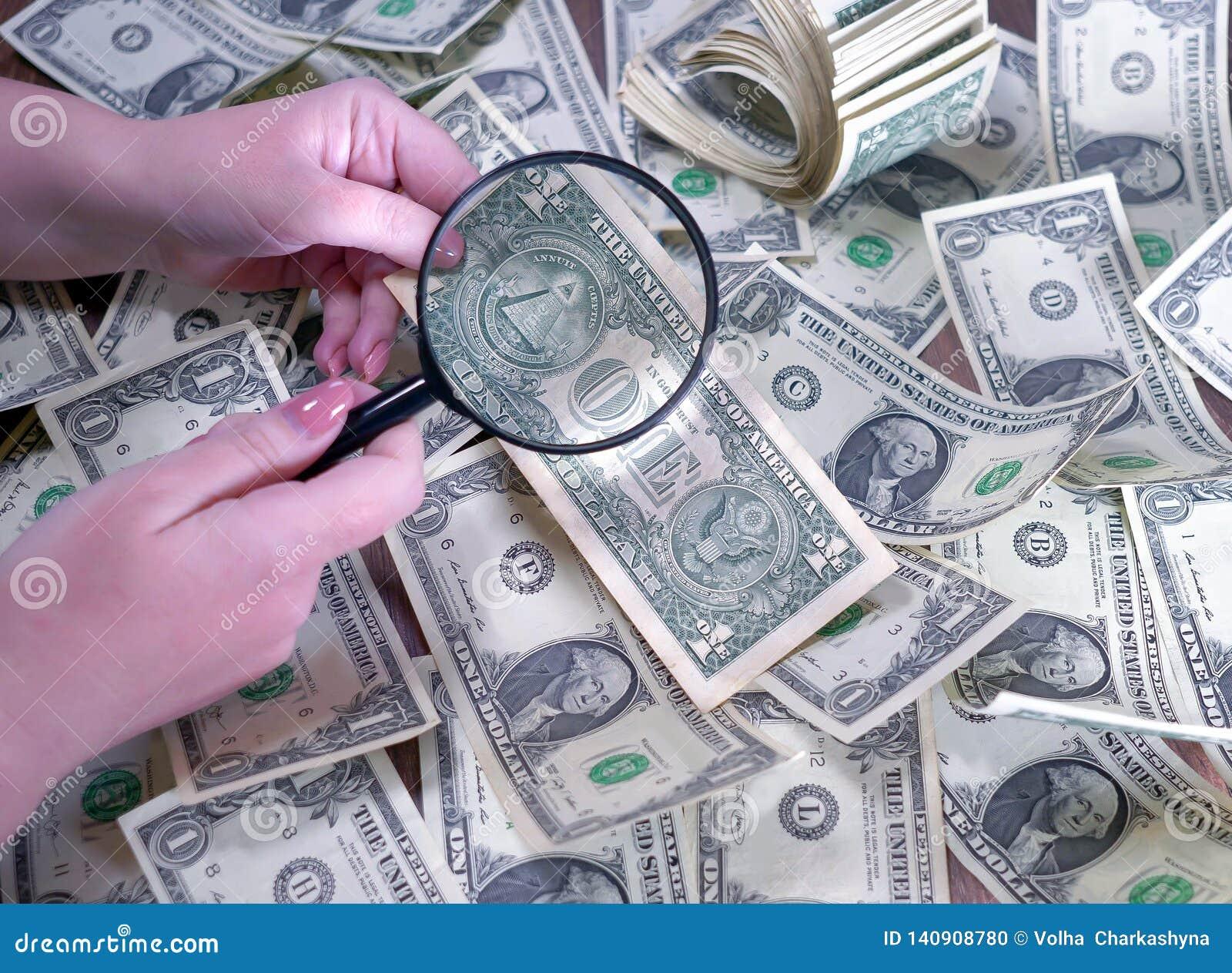 Examine des dollars par une loupe à disposition