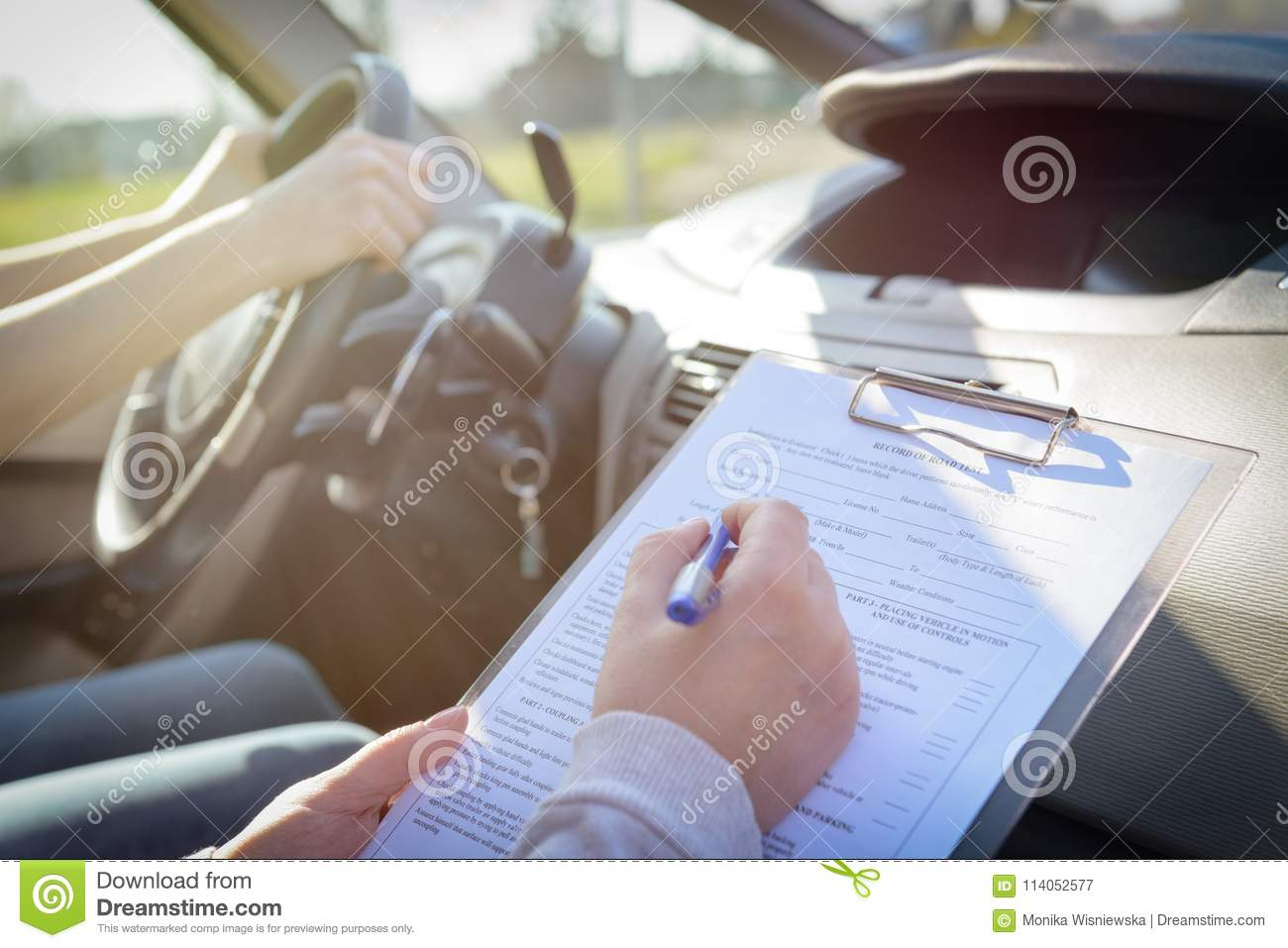 Examiner filling in driver`s license road test form
