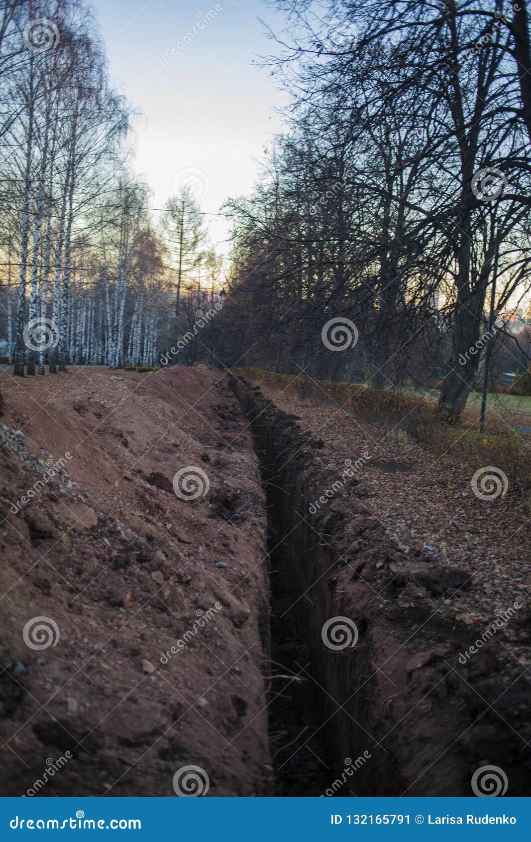 Excavación de un foso Terraplénes, foso de excavación Foso de tierra largo cavado para poner el tubo o la fibra óptica