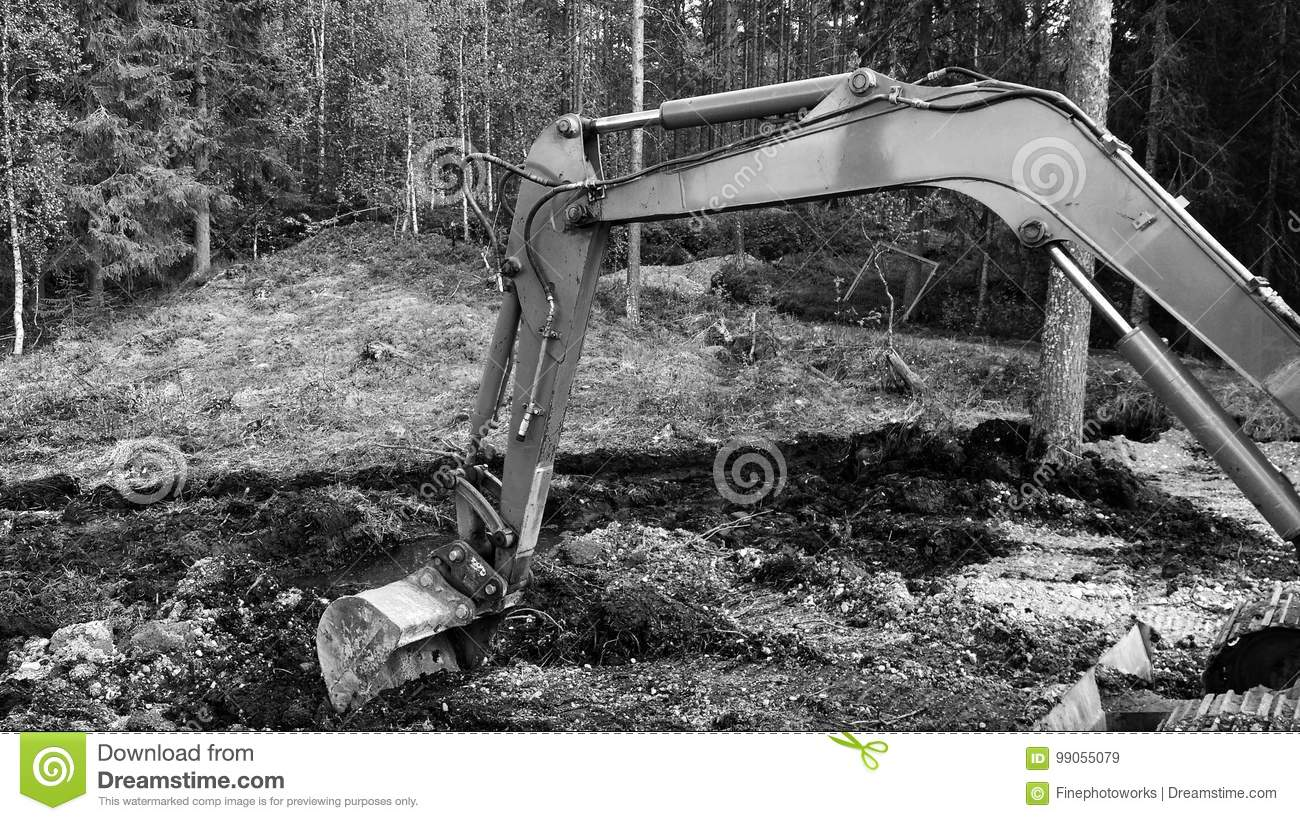 Excavator arm digging in mud background black and white