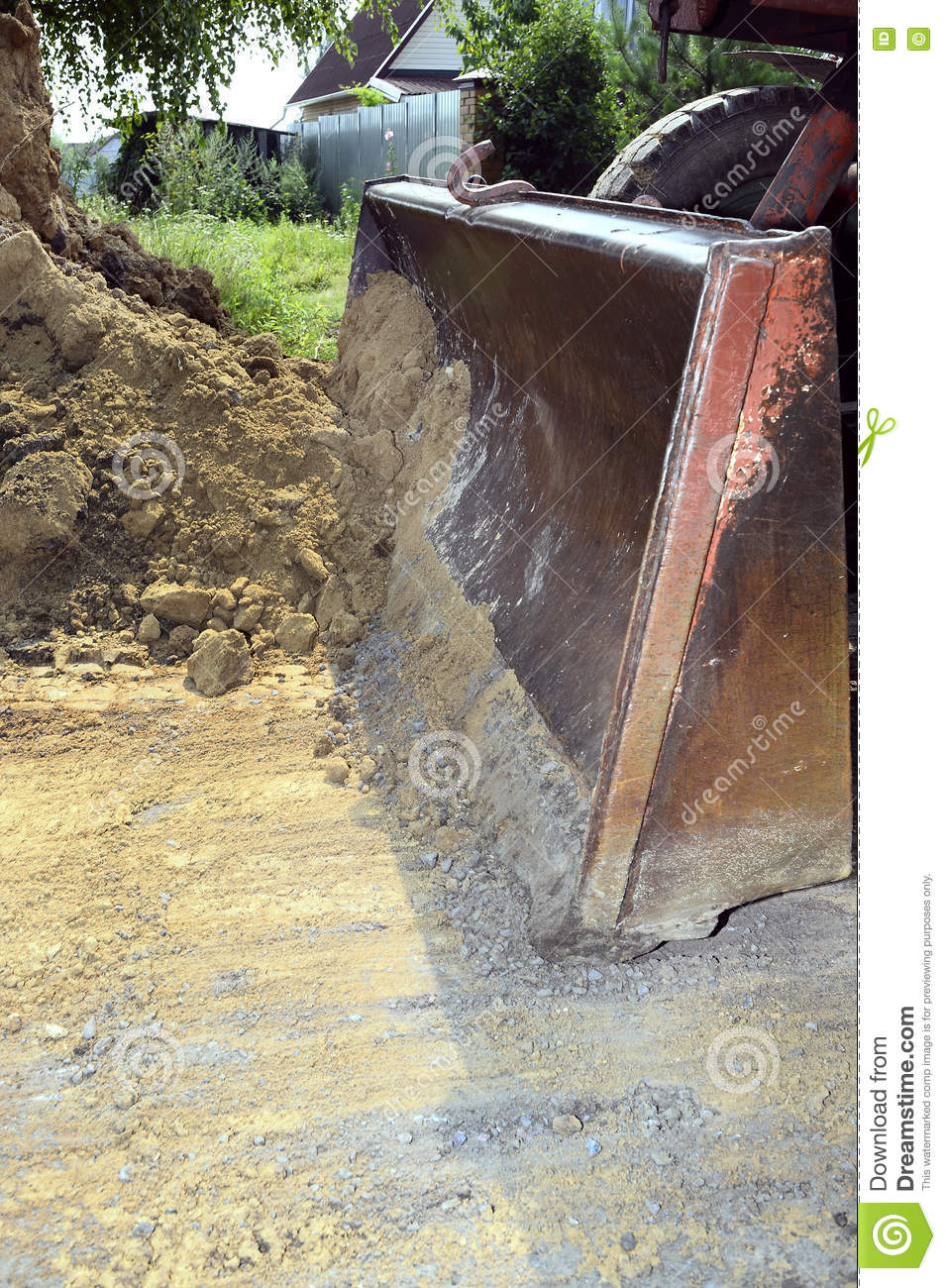 Excavator bucket digging a trench in the dirt ground stock for Digging ground dream meaning