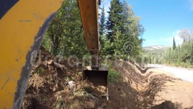 Excavator with bucket digging a trench