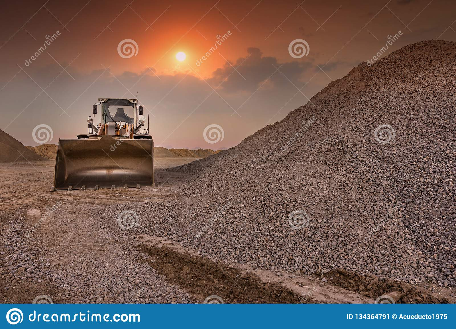 Excavator in a quarry of stone transformation in gravel for the construction of a road