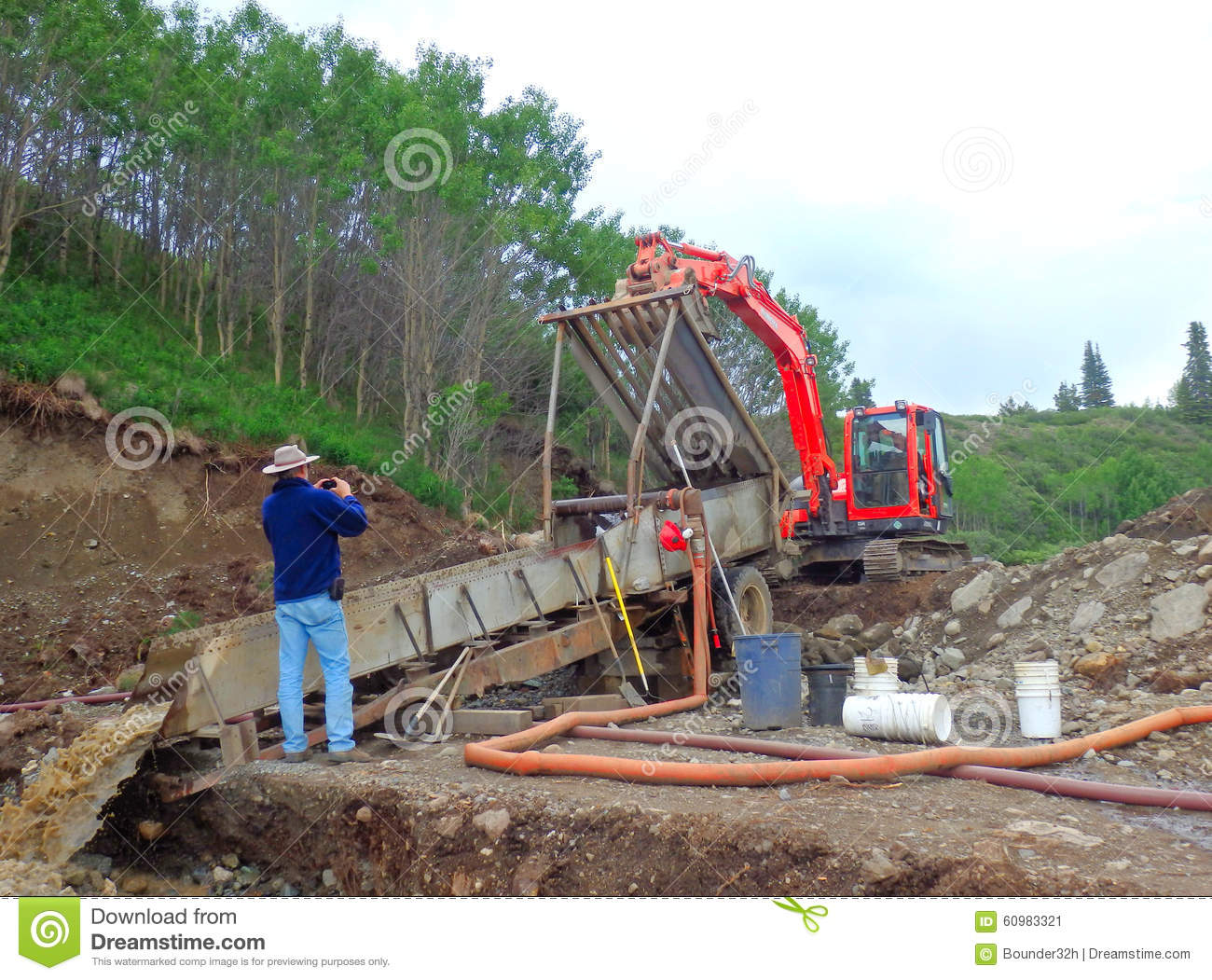 An excavator screening pay dirt at a gold claim in northern bc