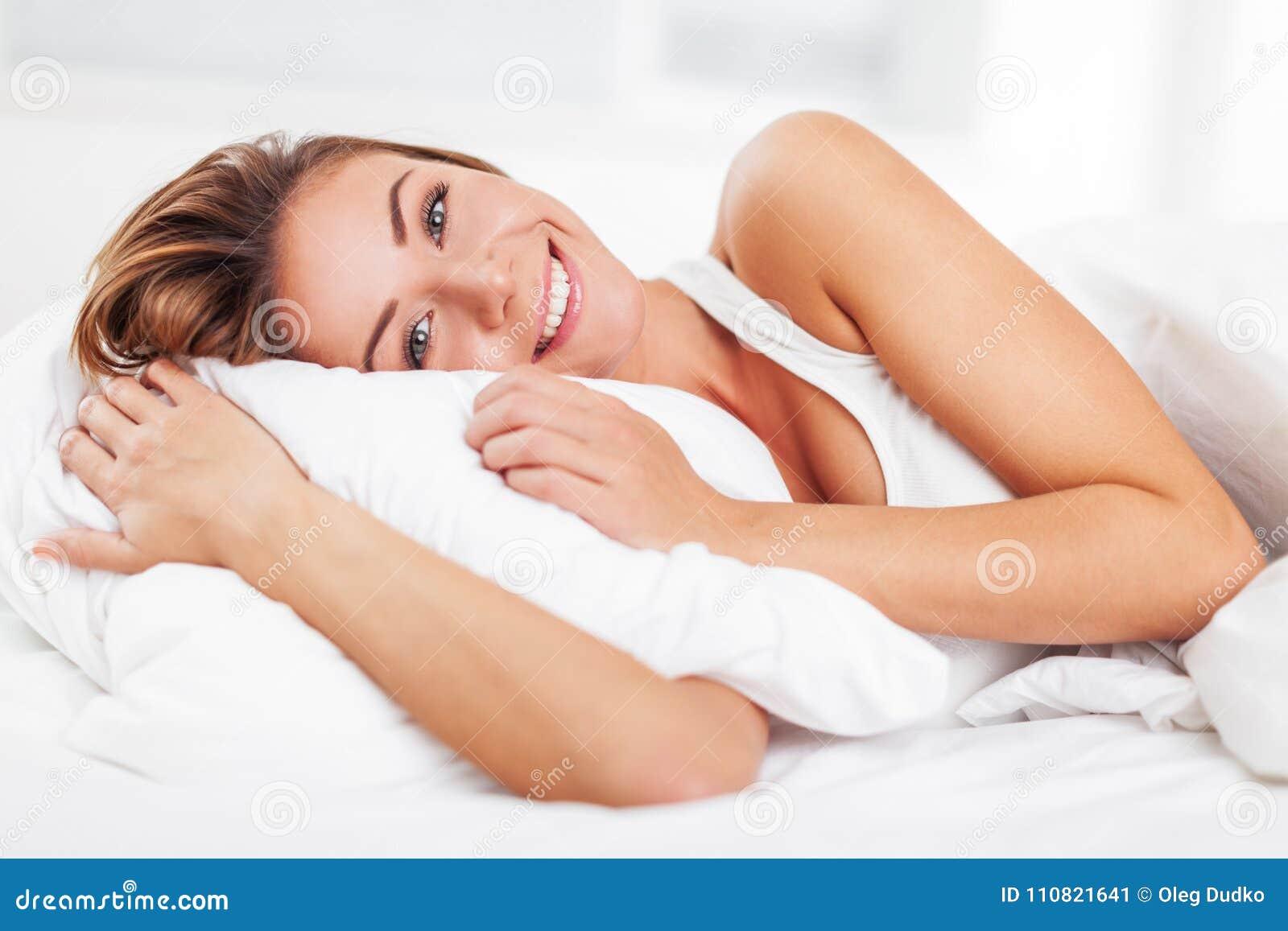 Excitação da jovem mulher após o sono no branco