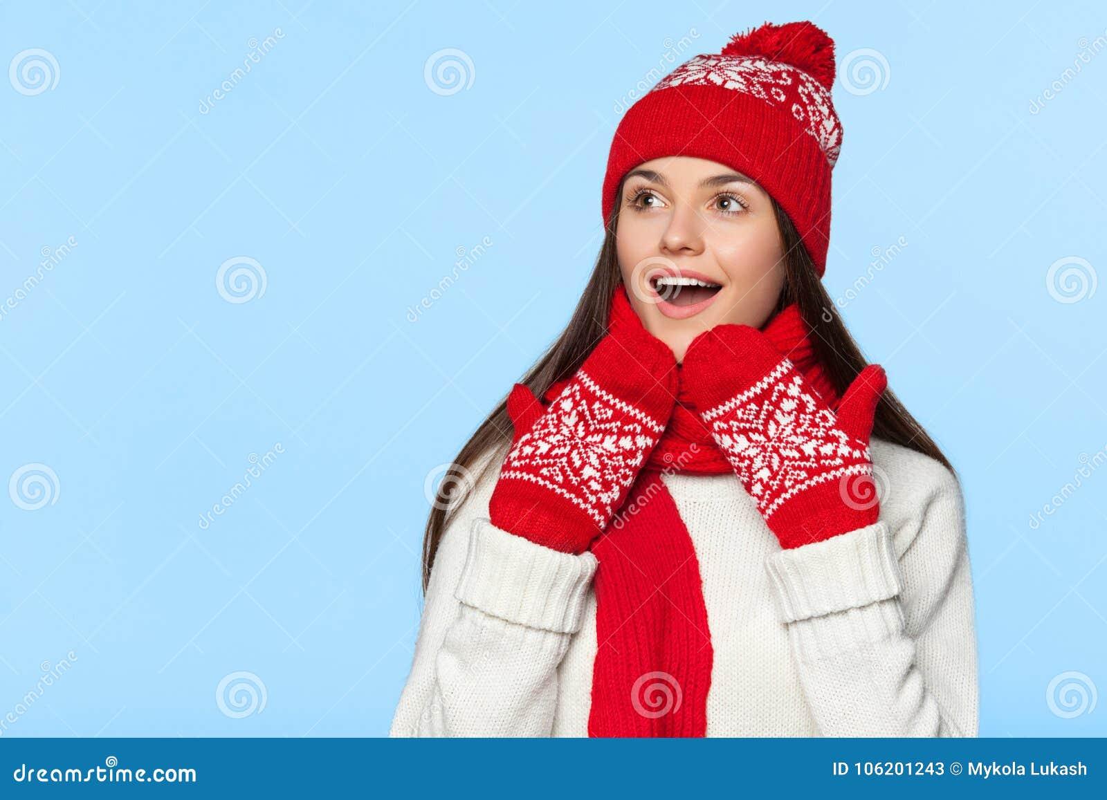 Excited женщина смотря косой в ободрении Удивленная девушка рождества нося связанную теплые шляпу и шарф, изолированные на сини