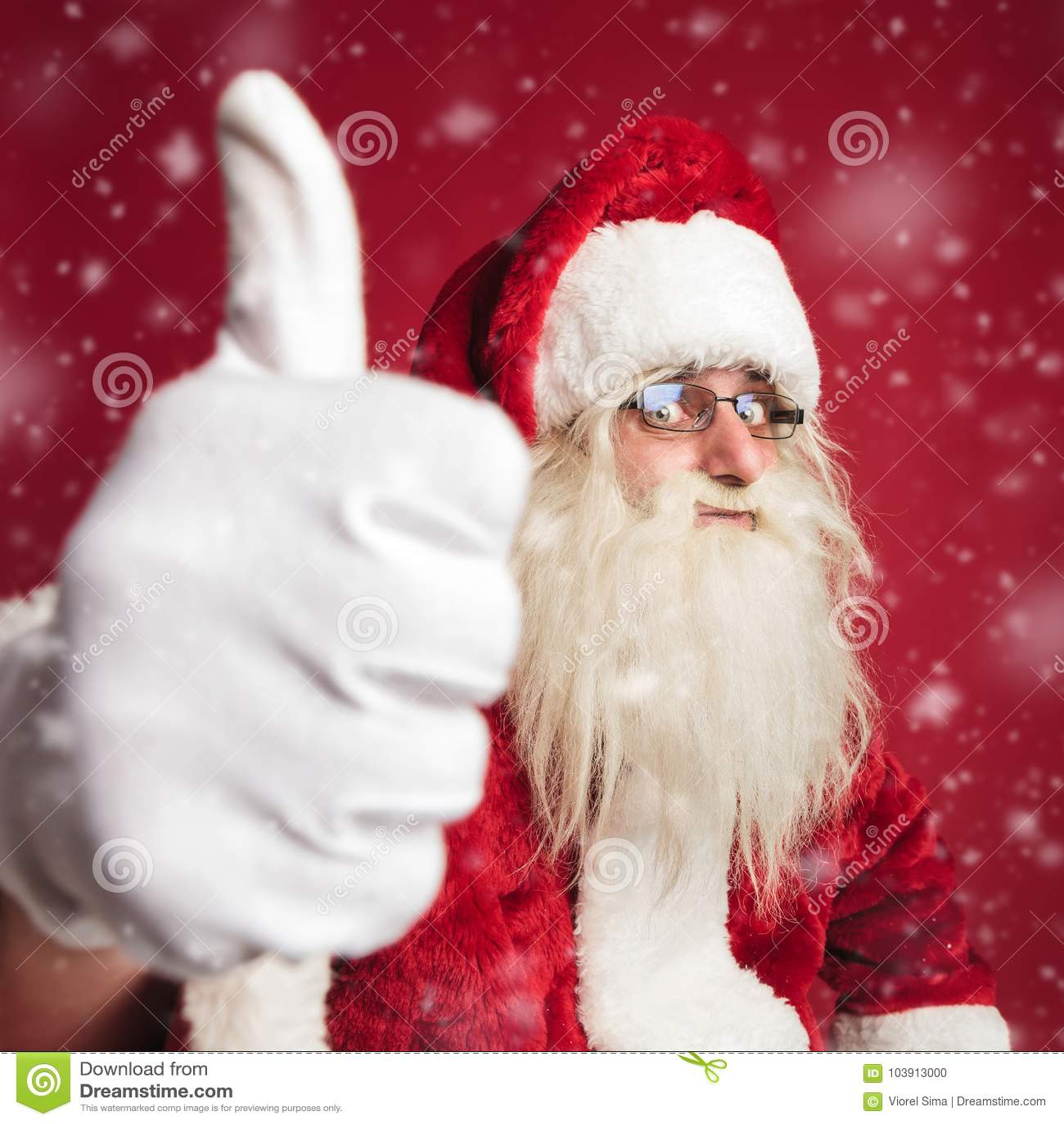 Excited Санта Клаус делая одобренный знак пока идущ снег