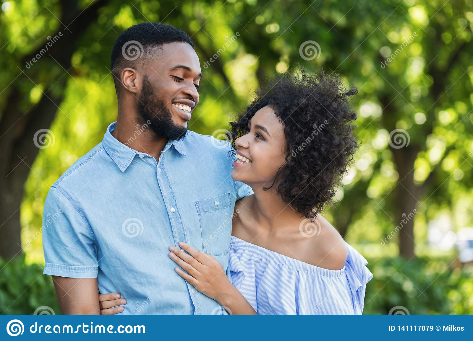 Excited black couple bonding while walking in park