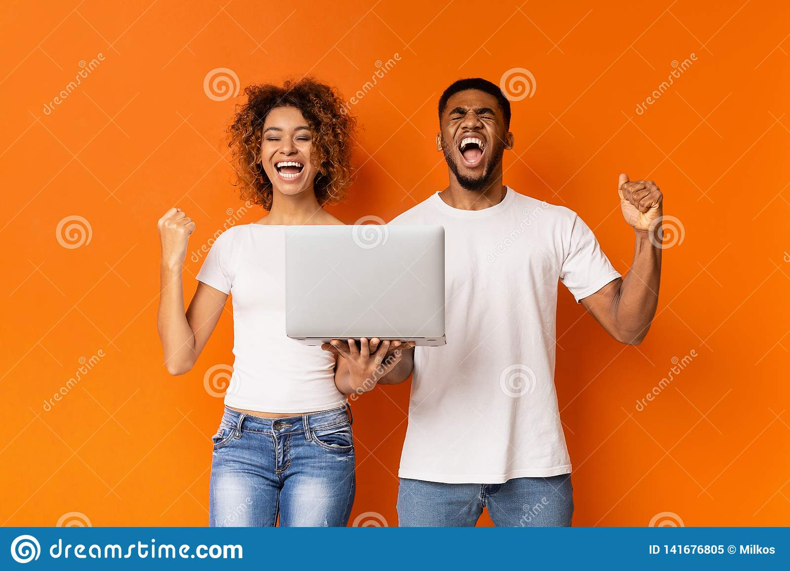 Excited black couple celebrating win with laptop