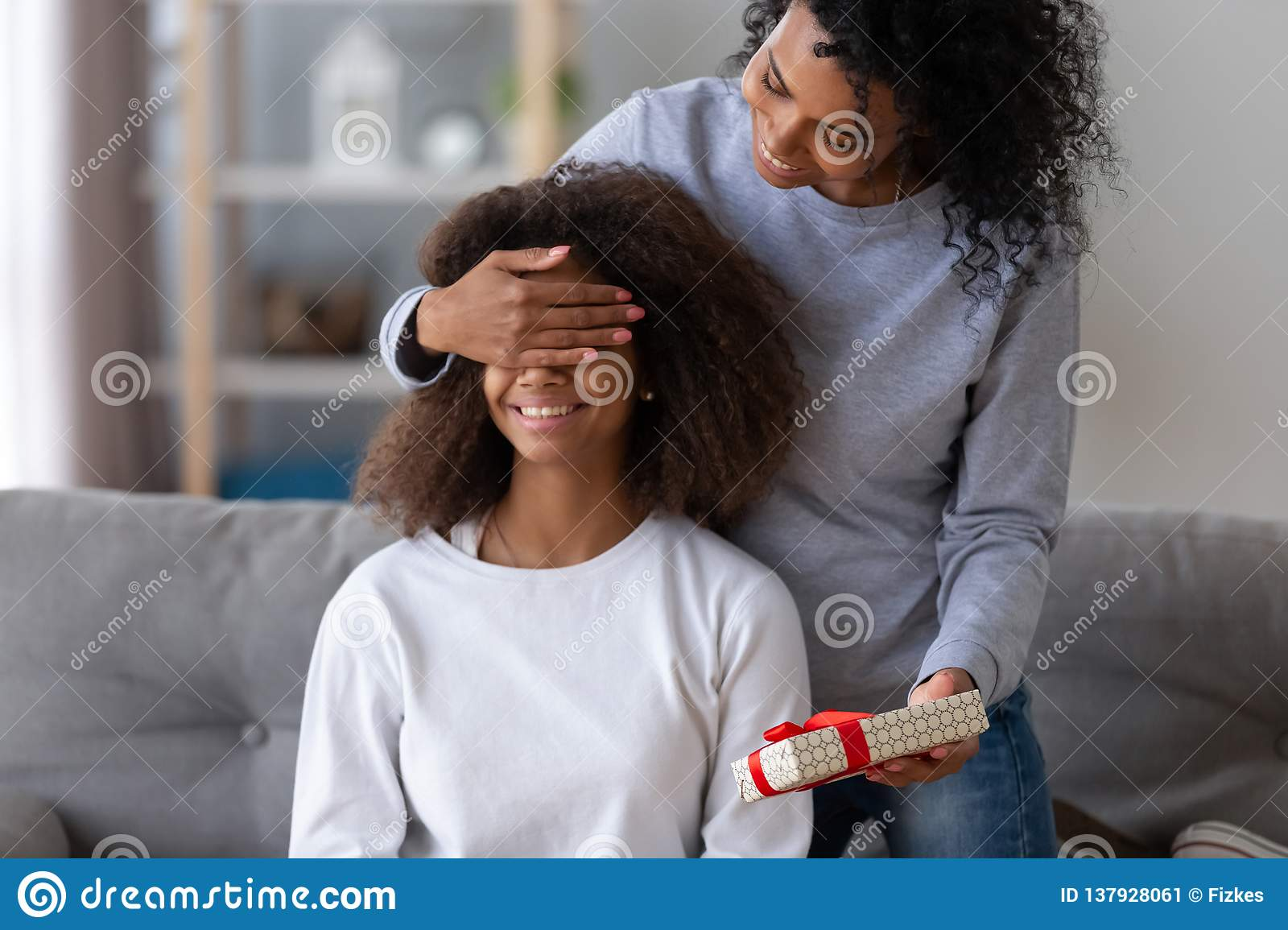Excited Black Young Mom Make Surprise For Teenage Daughter Happy African American Mother Close Child Eyes Presenting Birthday Gift Relaxing At Home