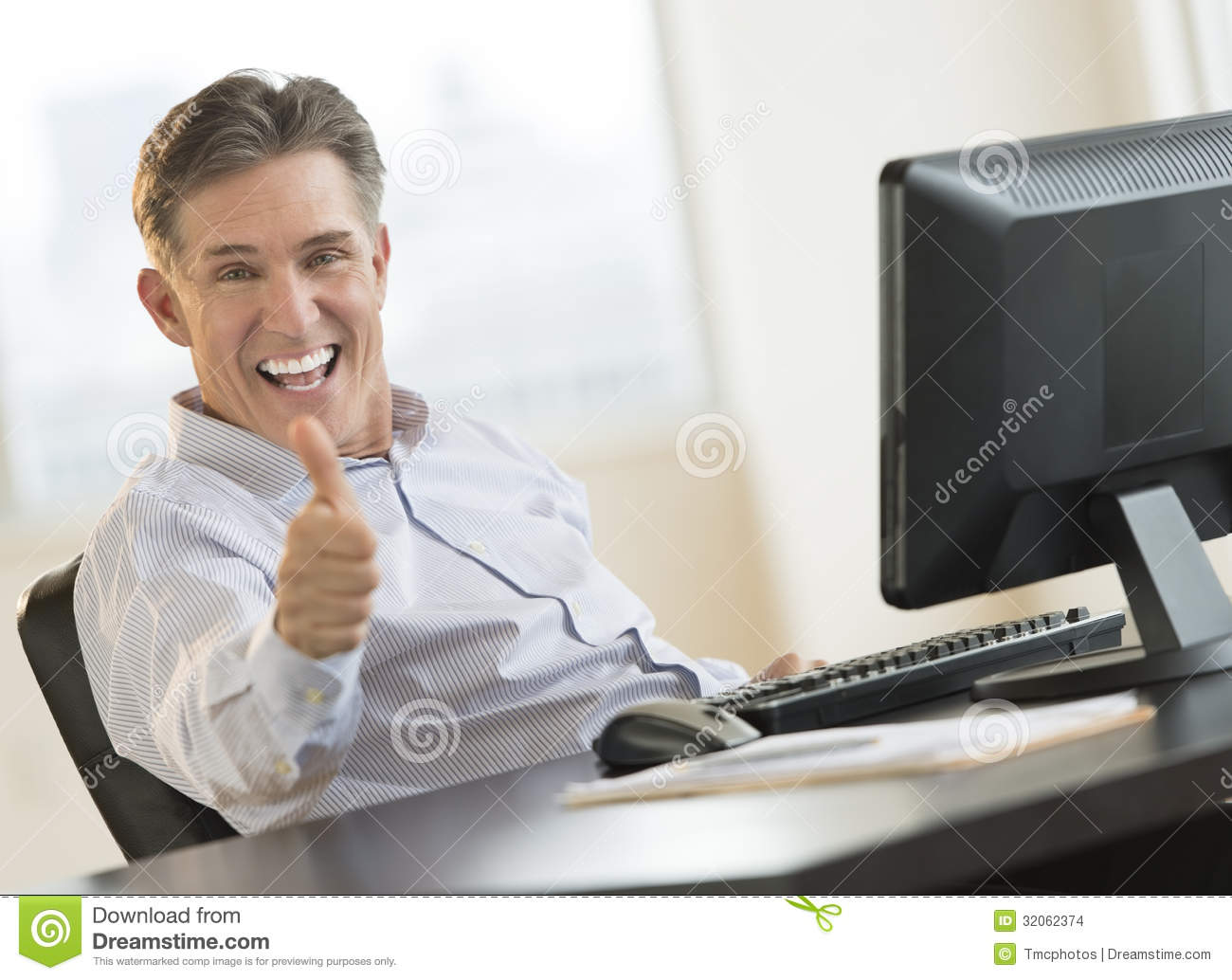 Excited Businessman Gesturing Thumbs Up At Desk Stock