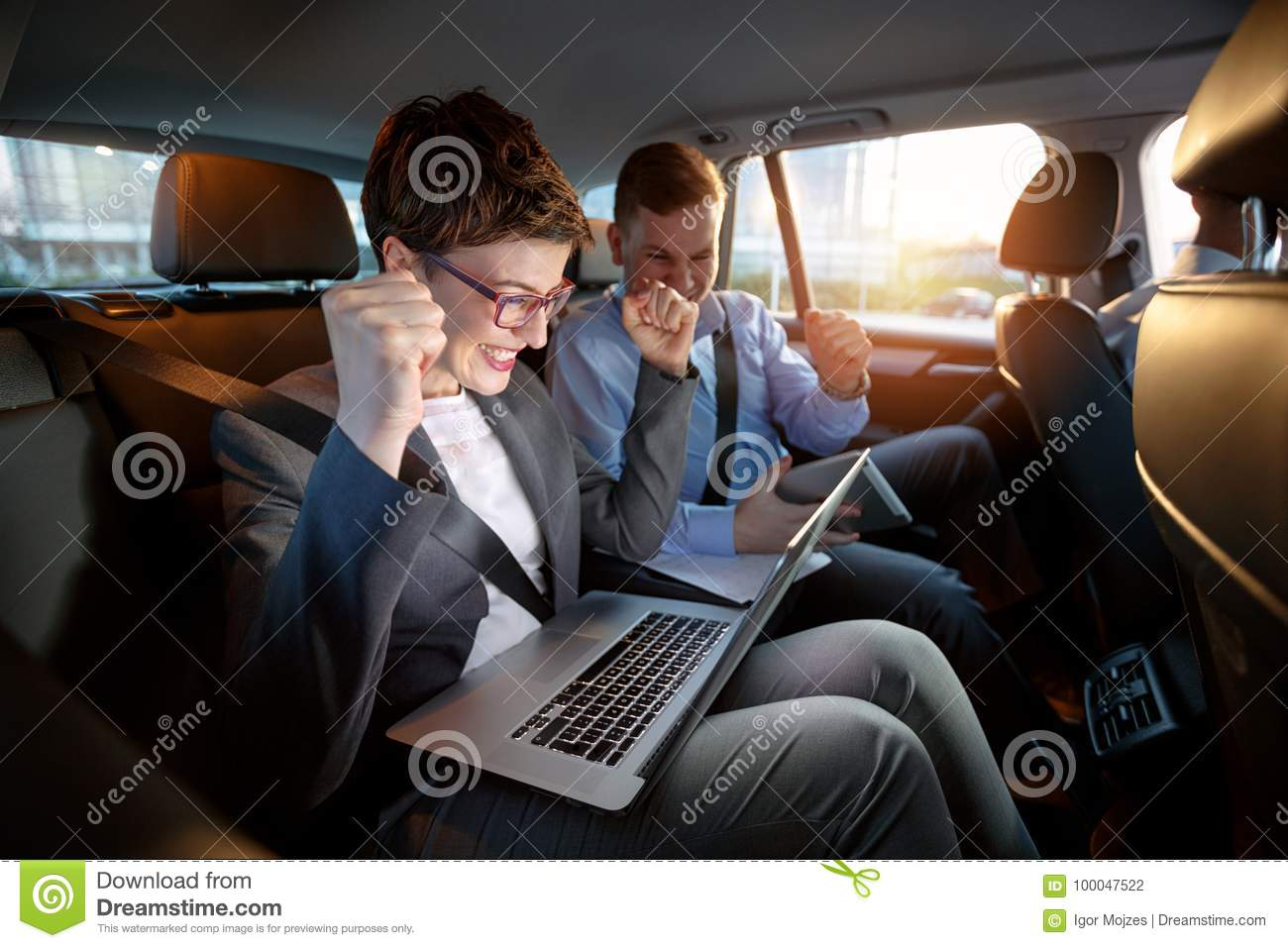 Excited businesspeople looking at laptop in car on trip